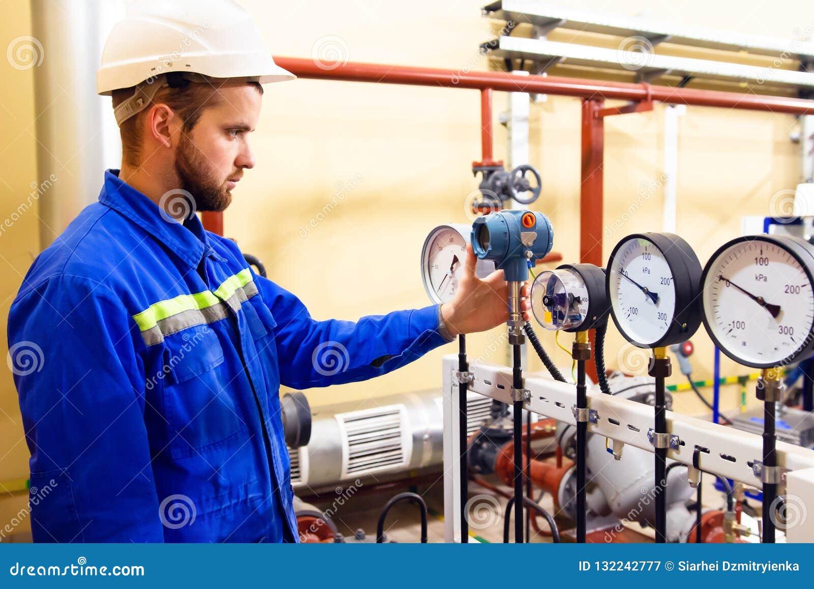 Εργαζόμενος τεχνικών στα μανόμετρα πίεσης ελέγχων εγκαταστάσεων καθαρισμού πετρελαίου και φυσικού αερίου