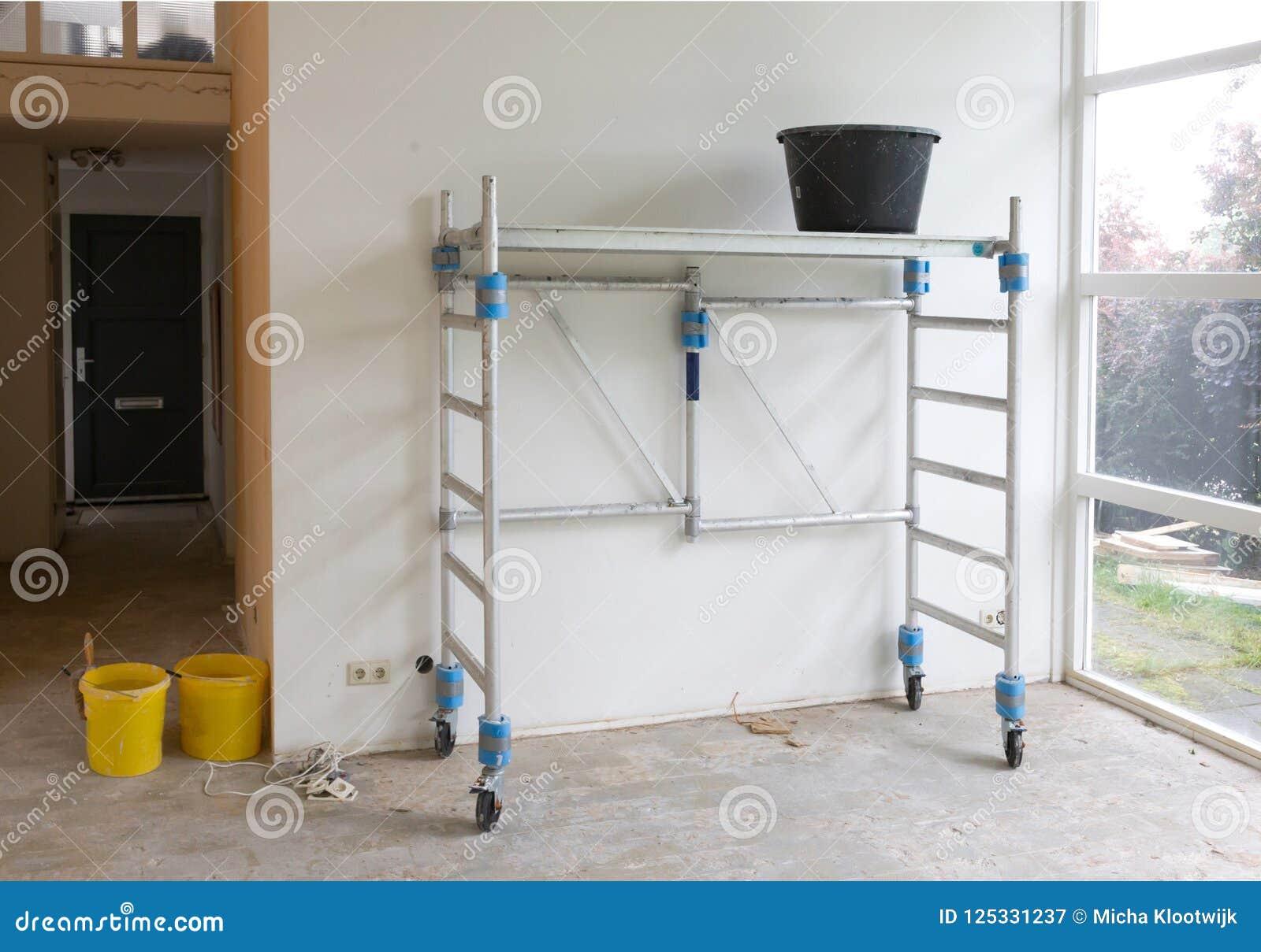 Εργαλεία εργαζομένων - κάδος που στέκεται στα κυλώντας υλικά σκαλωσιάς