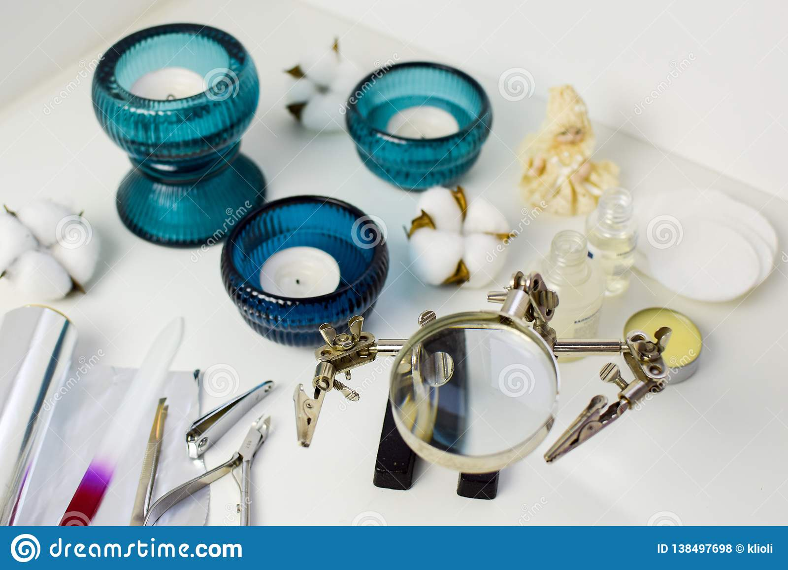 Εργαλεία μανικιούρ, κεριά στα τυρκουάζ κηροπήγια, βαμβάκι και κεραμική κούκλα, ασυνήθιστη ενίσχυση - γυαλί