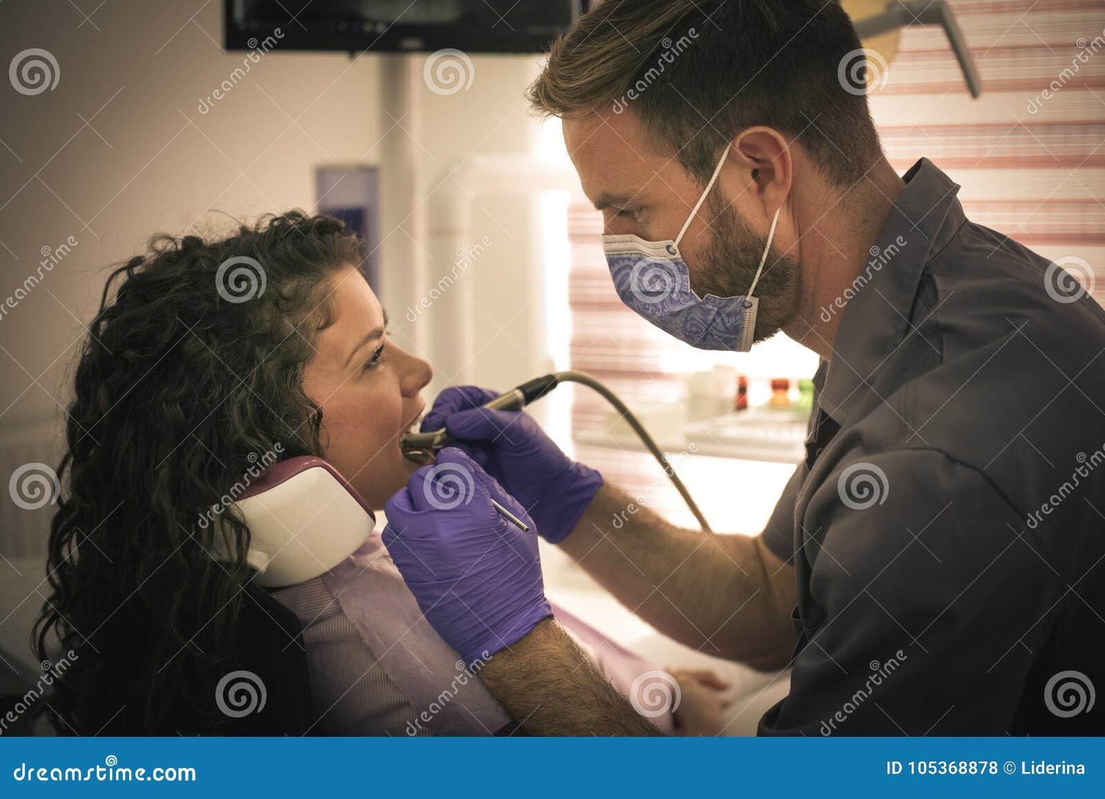 Εργασία οδοντιάτρων με το τρυπάνι στον ασθενή