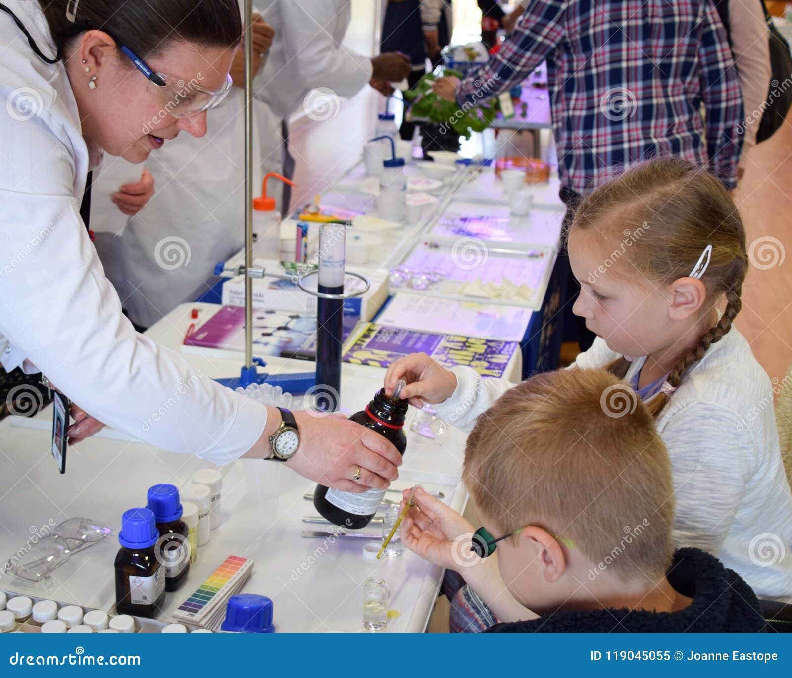 Εργαστηριακοί φαρμακοποιοί tak μια ημέρα από το εργαστήριο για να διδάξει τα παιδιά για τη χημεία ως τμήμα του βρετανικού ΜΙΣΧΟΥ,