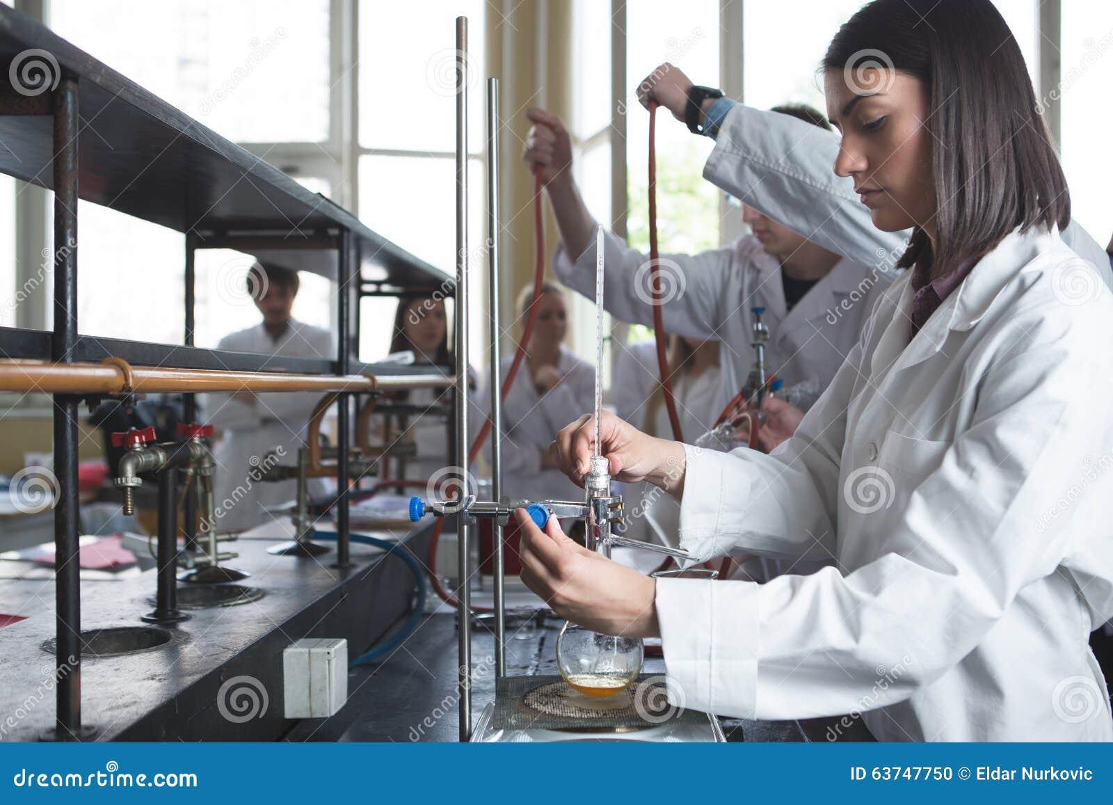Εργαστηριακός εξοπλισμός για την απόσταξη Χέρια σπουδαστών/οικότροφων/του τεχνικού που παρουσιάζουν πείραμα Εργασία στις ομάδες γ