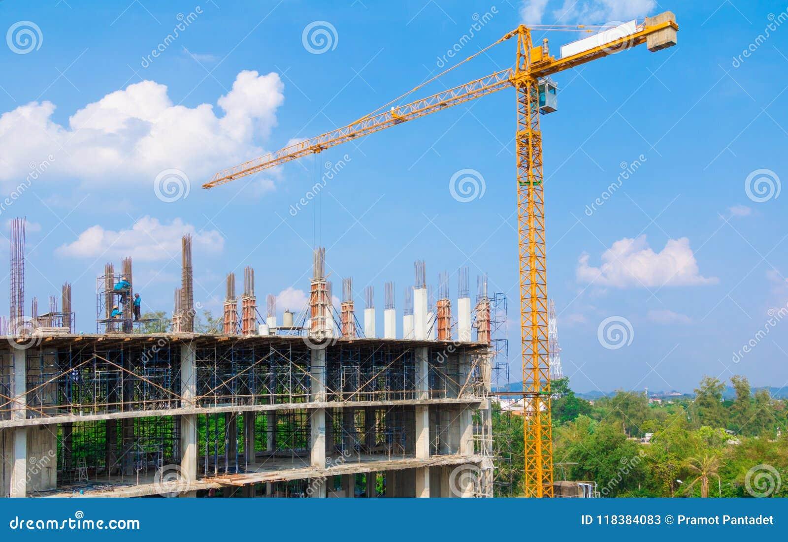 Εργοτάξιο και οικοδόμηση της κατοικίας στην εργασία laborer υπαίθρια που έχει το υπόβαθρο μπλε ουρανού γερανών πύργων με το αντίγ