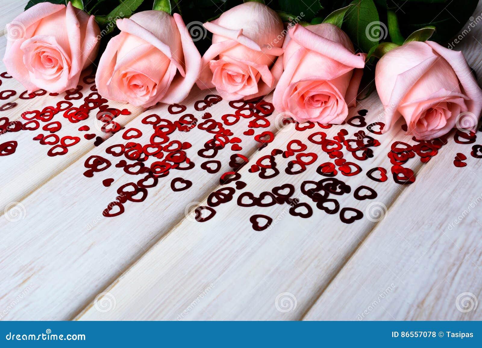 Ερωτευμένη έννοια πτώσης με χλωμό - ρόδινα τριαντάφυλλα και μικρές κόκκινες καρδιές