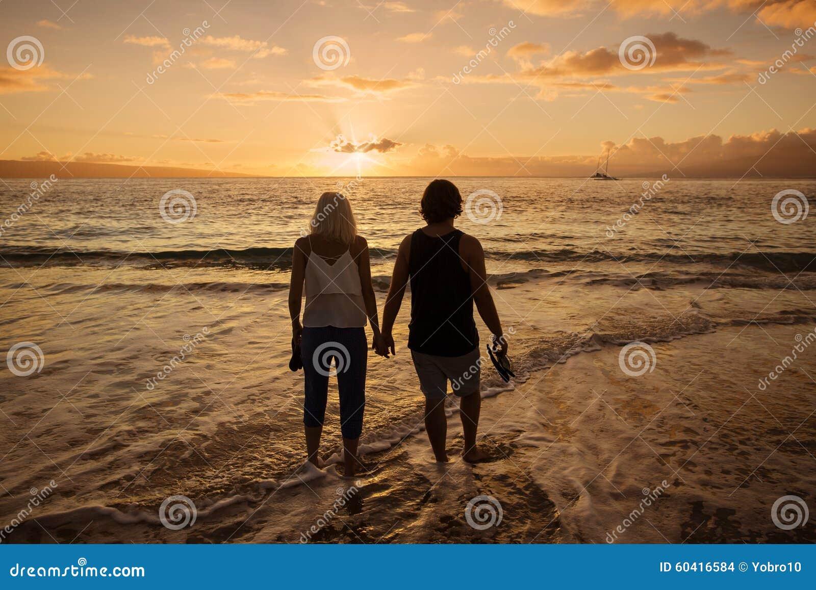 Ερωτευμένο περπάτημα ζεύγους κατά μήκος της παραλίας μαζί στο ηλιοβασίλεμα