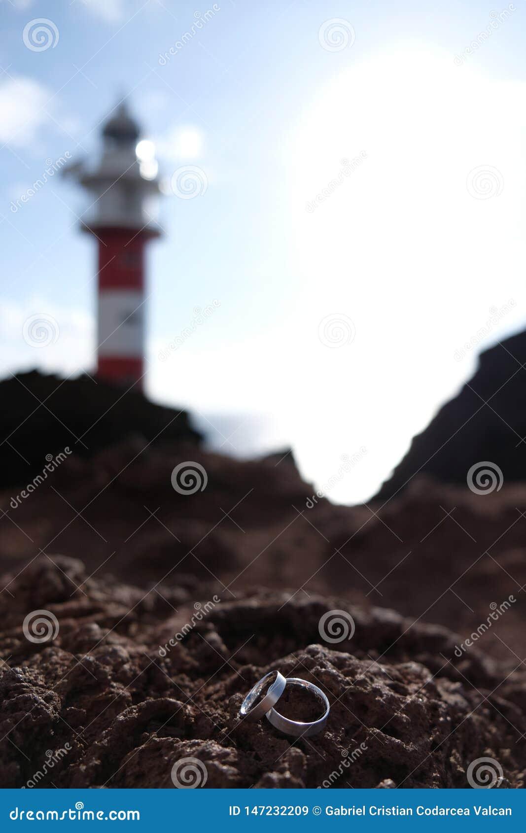 Εστίαση στα γαμήλια δαχτυλίδια στον ηφαιστειακό βράχο με το θολωμένο κόκκινο και άσπρο φάρο στο υπόβαθρο
