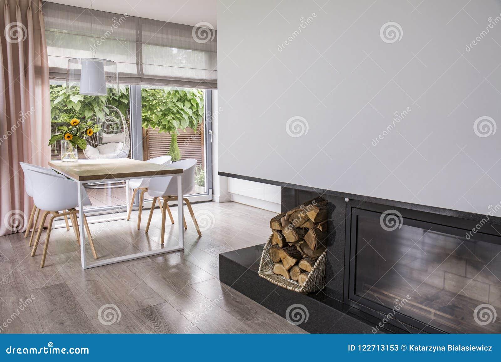 Εστία δίπλα στις άσπρες καρέκλες στον πίνακα στο φωτεινό εσωτερικό τραπεζαρίας με το παράθυρο Πραγματική φωτογραφία
