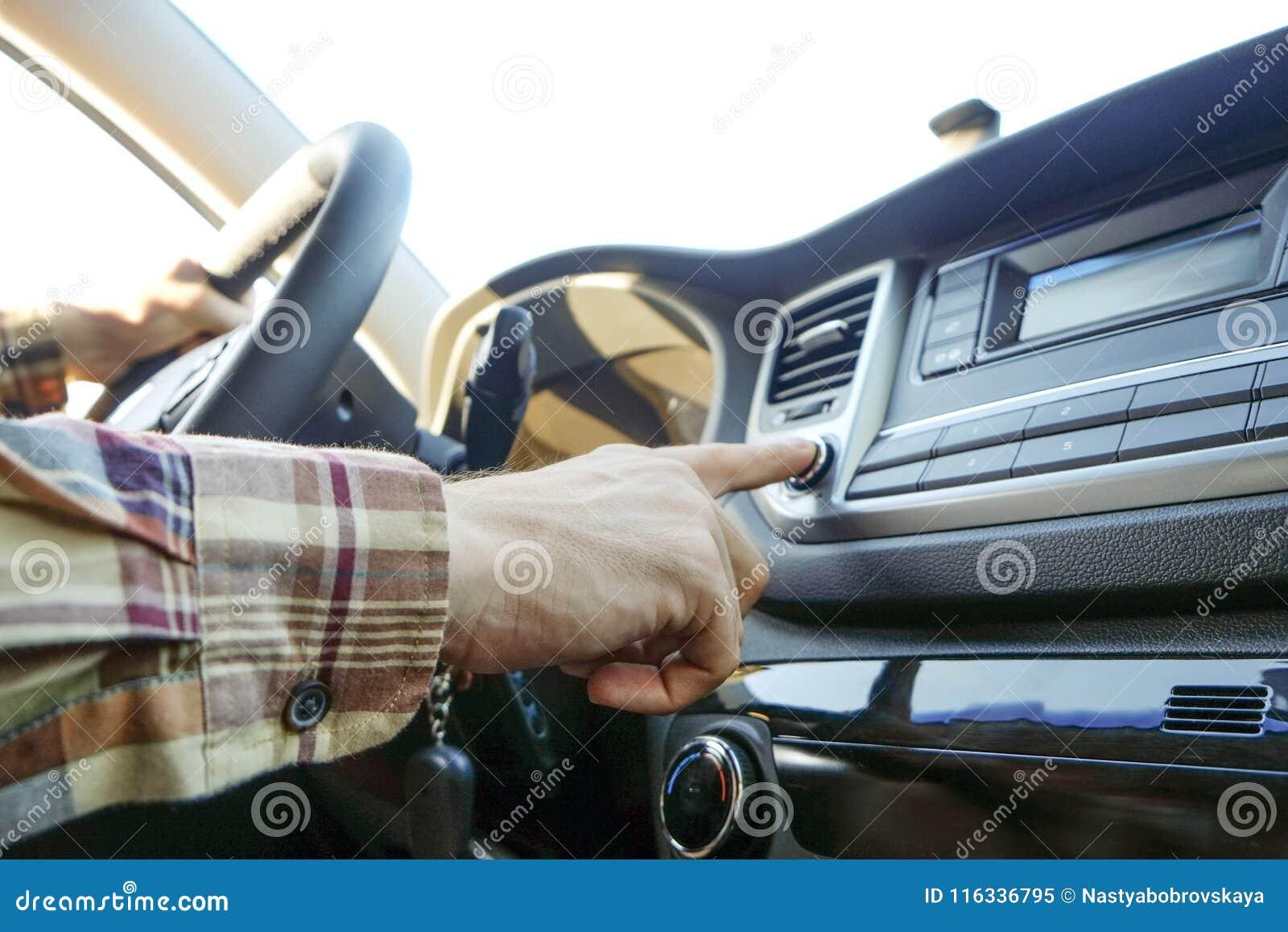 Εσωτερικό αυτοκινήτων με την αρσενική συνεδρίαση οδηγών πίσω από τη ρόδα, μαλακό φως ηλιοβασιλέματος Πολυτελές ταμπλό και ηλεκτρο