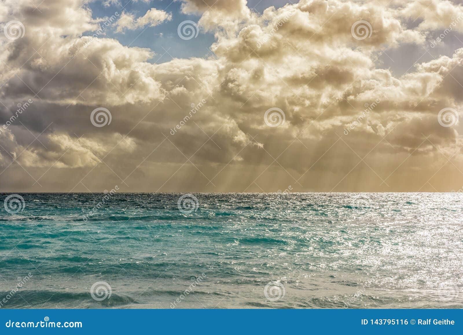 Ευγενής θάλασσα με τα μικρά κύματα και ένας όμορφος νεφελώδης ουρανός με τις ηλιαχτίδες
