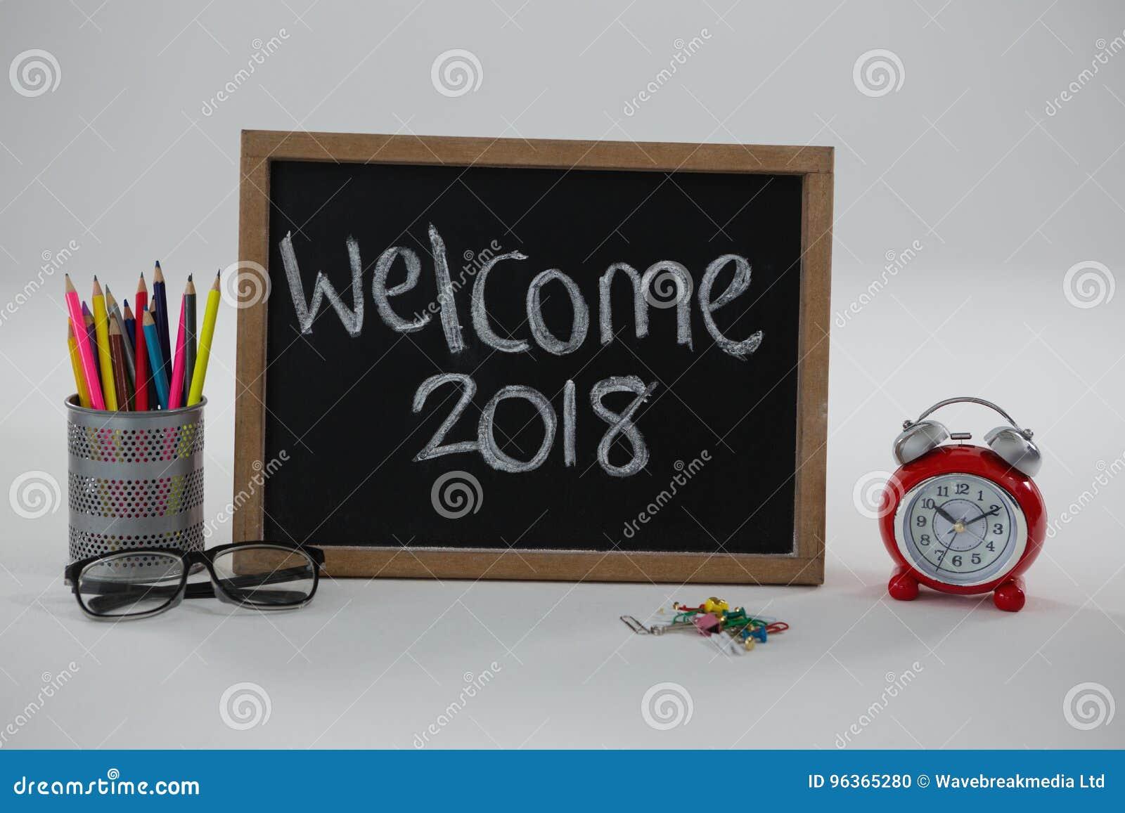 Ευπρόσδεκτο κείμενο του 2018 στον πίνακα κιμωλίας με τις διάφορες σχολικές προμήθειες