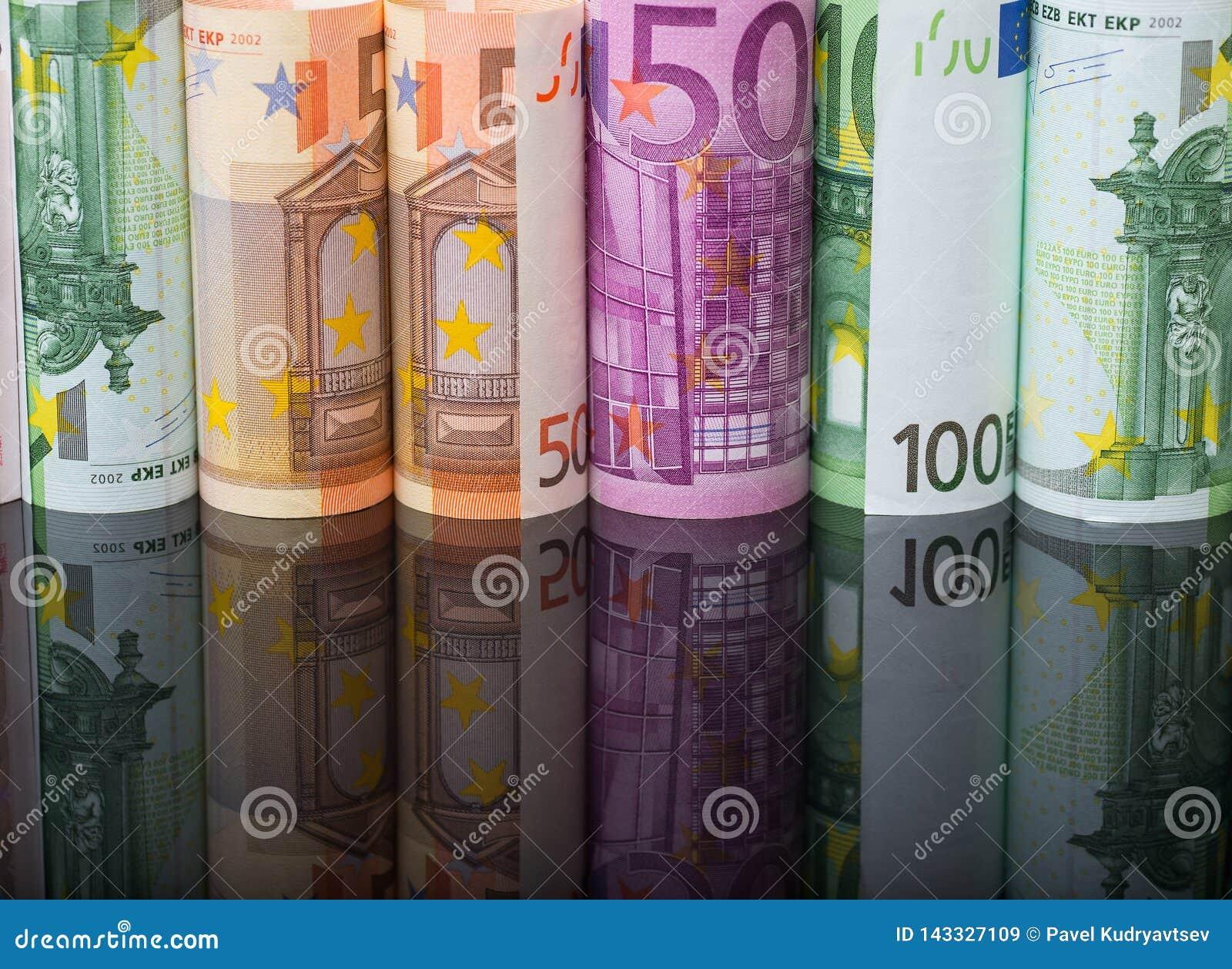 Ευρωπαϊκά χρήματα εγγράφου στους ρόλους στο μαύρο υπόβαθρο με την αντανάκλαση