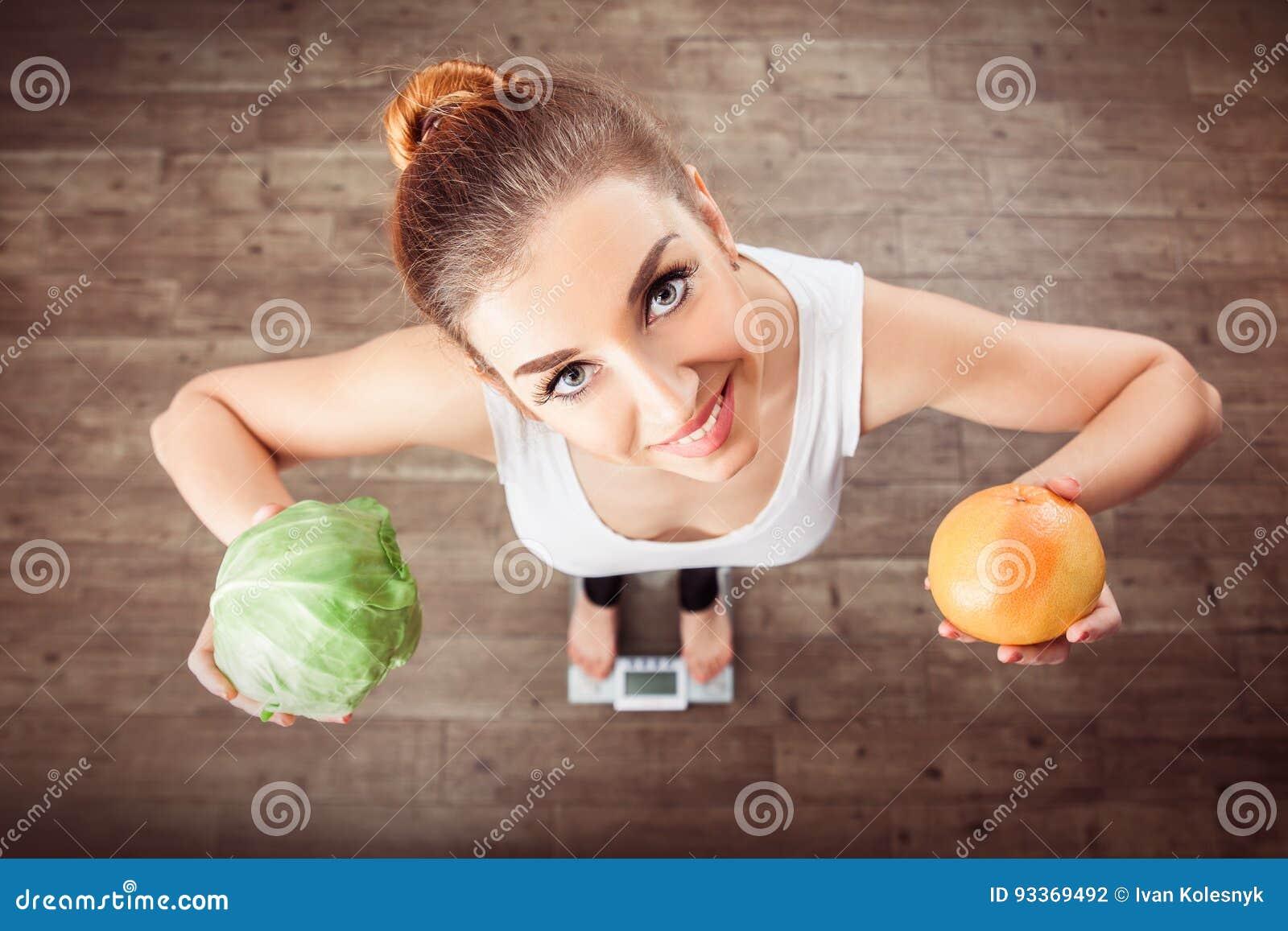 Ευρωπαϊκές στάσεις κοριτσιών στις κλίμακες και την εκμετάλλευση ένα λάχανο και grapefr