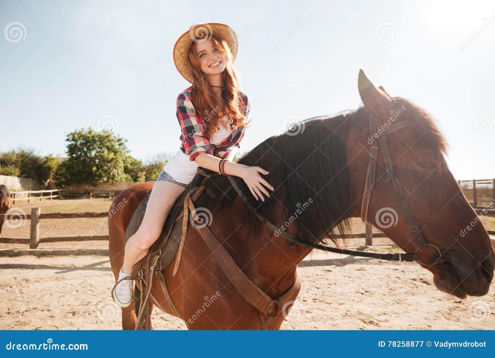 Ευτυχές άλογο οδήγησης γυναικών cowgirl στο αγρόκτημα