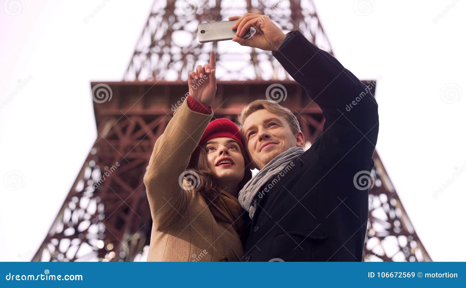Ευτυχές αγαπώντας ζεύγος των τουριστών που κάνουν selfie στο υπόβαθρο του πύργου του Άιφελ