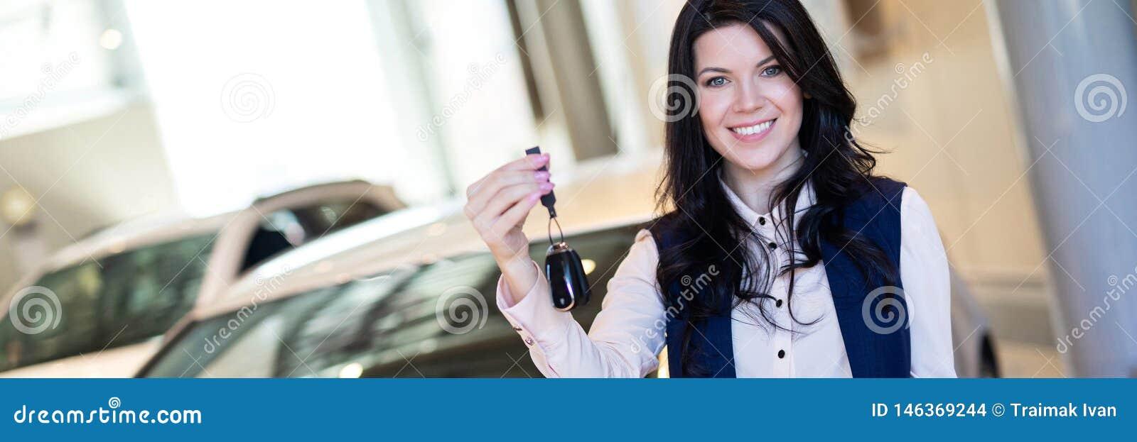 Ευτυχές αγοραστών γυναικών με τα κλειδιά κοντά στο νέο όχημά της στη εμπορία αυτοκινήτων