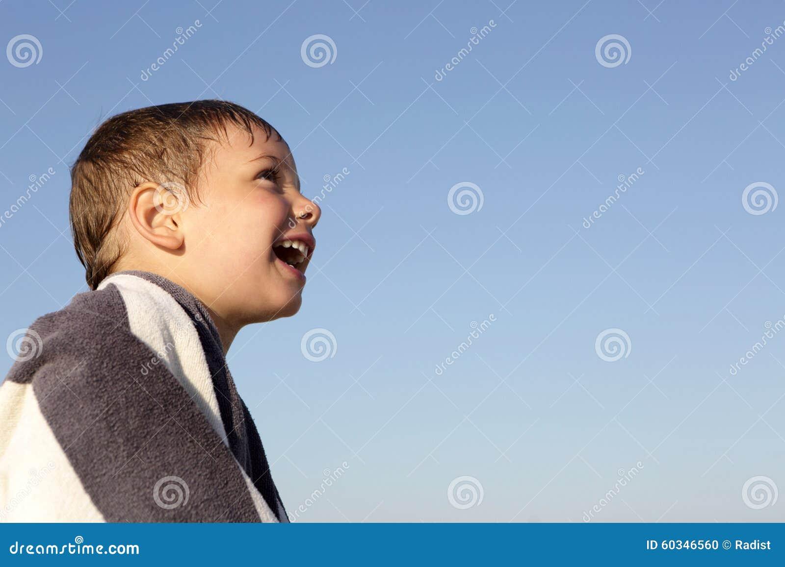 Ευτυχές αγόρι σε ένα υπόβαθρο ουρανού