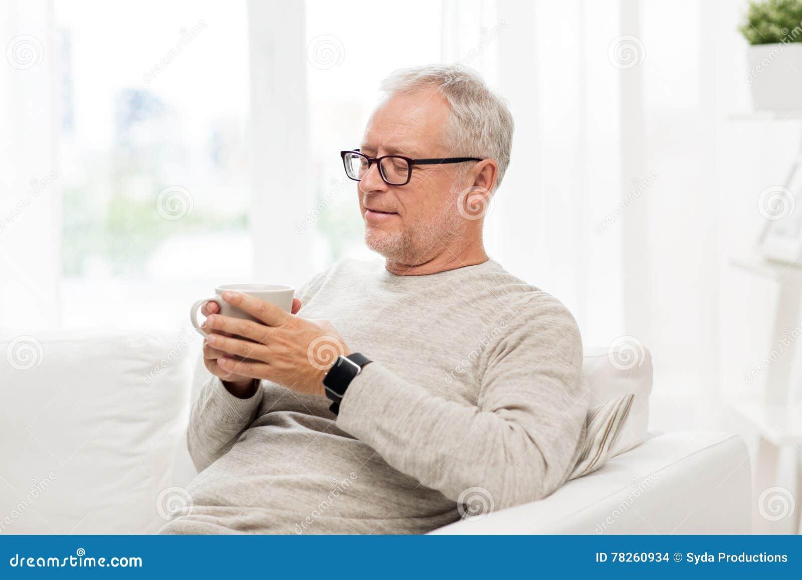 Ευτυχές ανώτερο άτομο με το φλυτζάνι του τσαγιού στο σπίτι