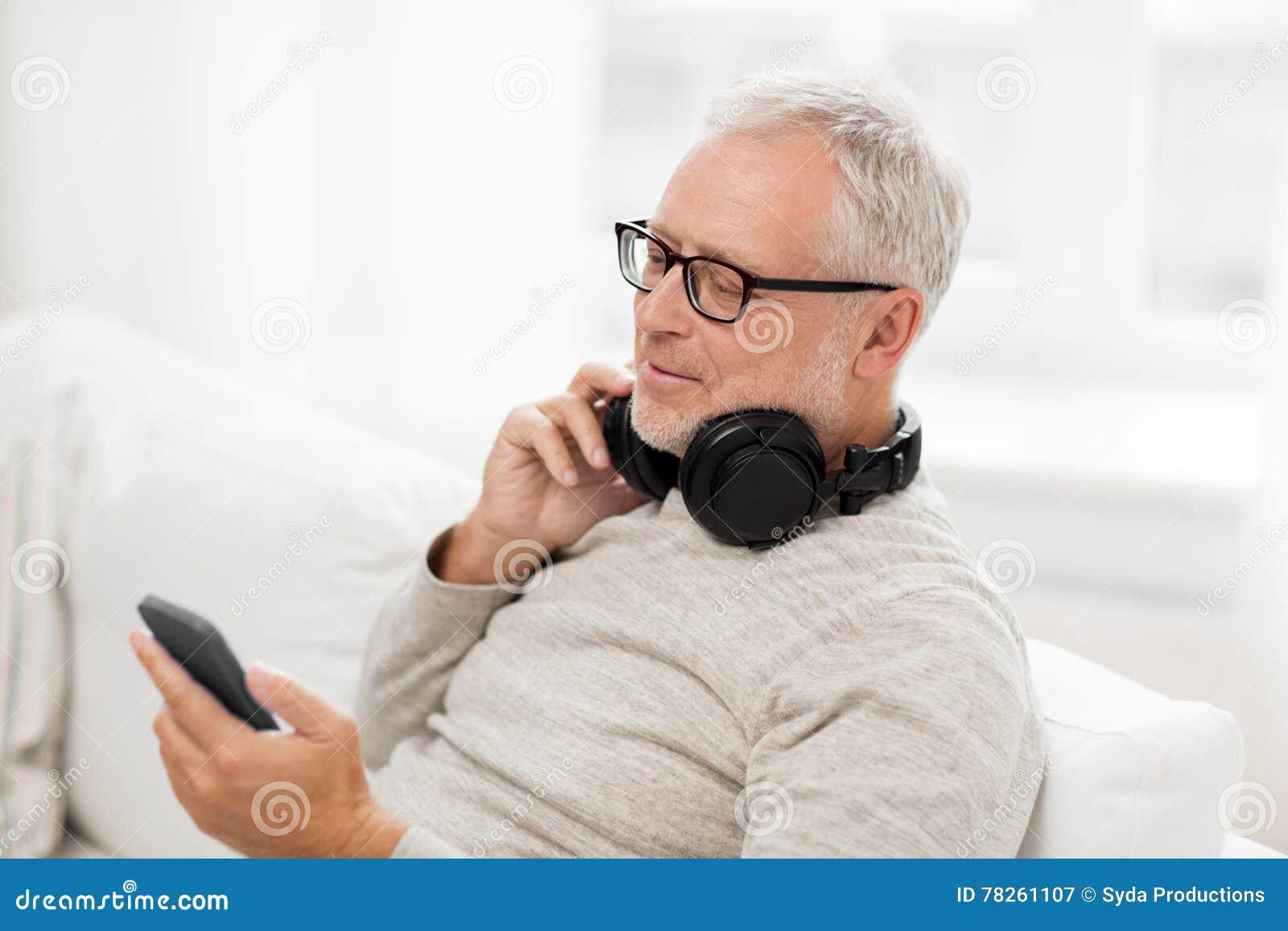 Ευτυχές ανώτερο άτομο με το smartphone και τα ακουστικά