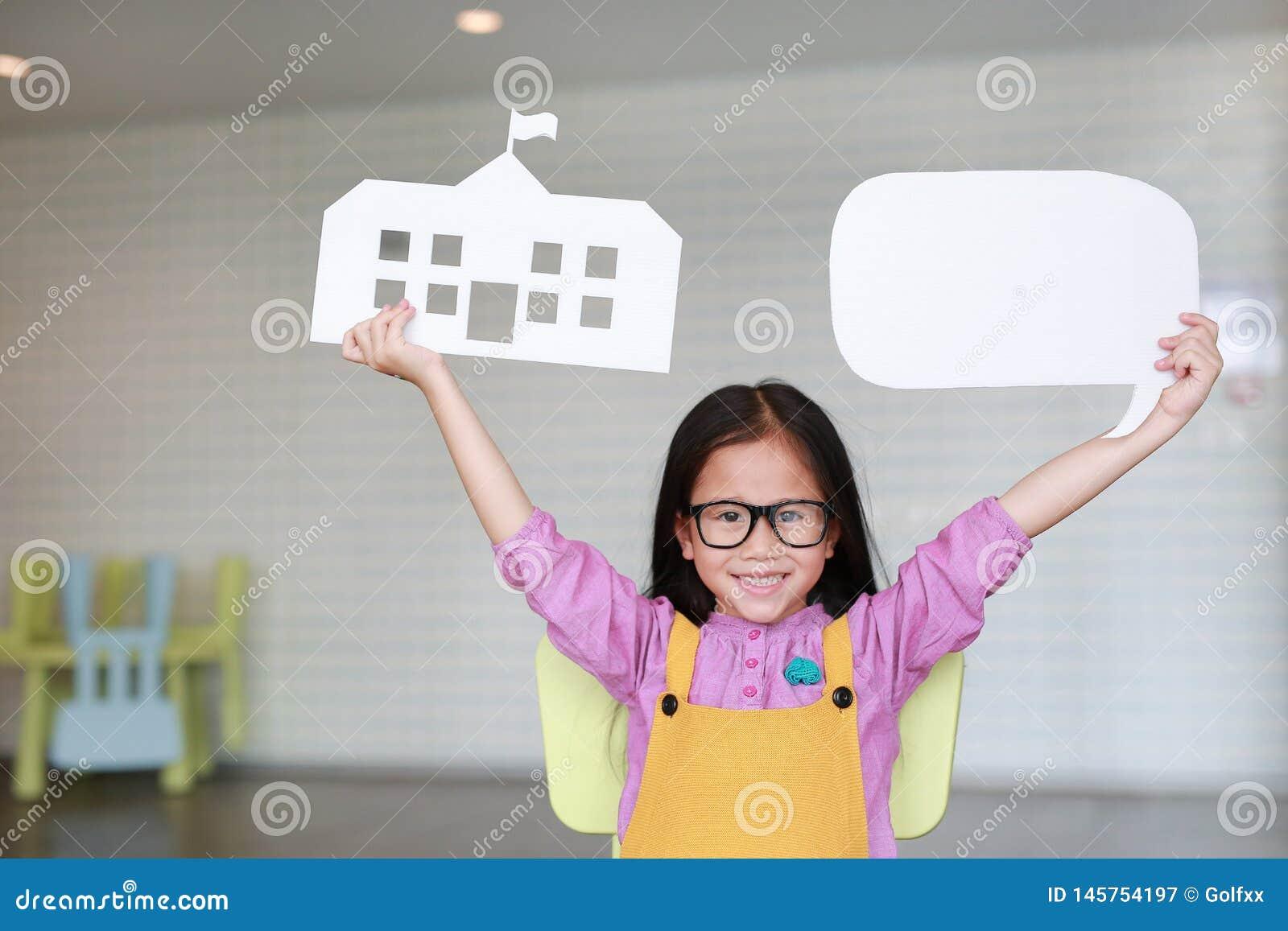 Ευτυχές ασιατικό μικρό κορίτσι στα ρόδινος-κίτρινα dungarees που κρατά το σχολείο εγγράφου προτύπων και την κενή κενή λεκτική φυσ