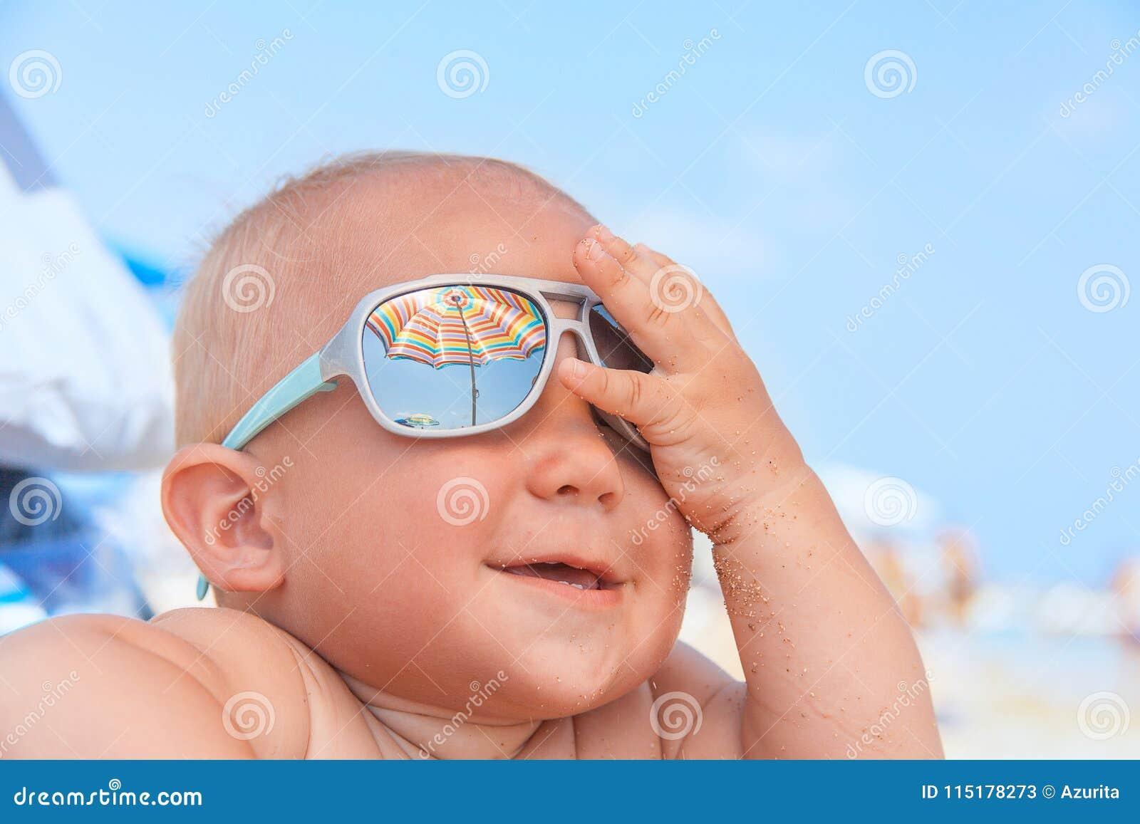c2b7933ca1 Λατρευτό ευτυχές αστείο χαμογελώντας χαριτωμένο αγοράκι με τα γυαλιά ηλίου  στην παραλία