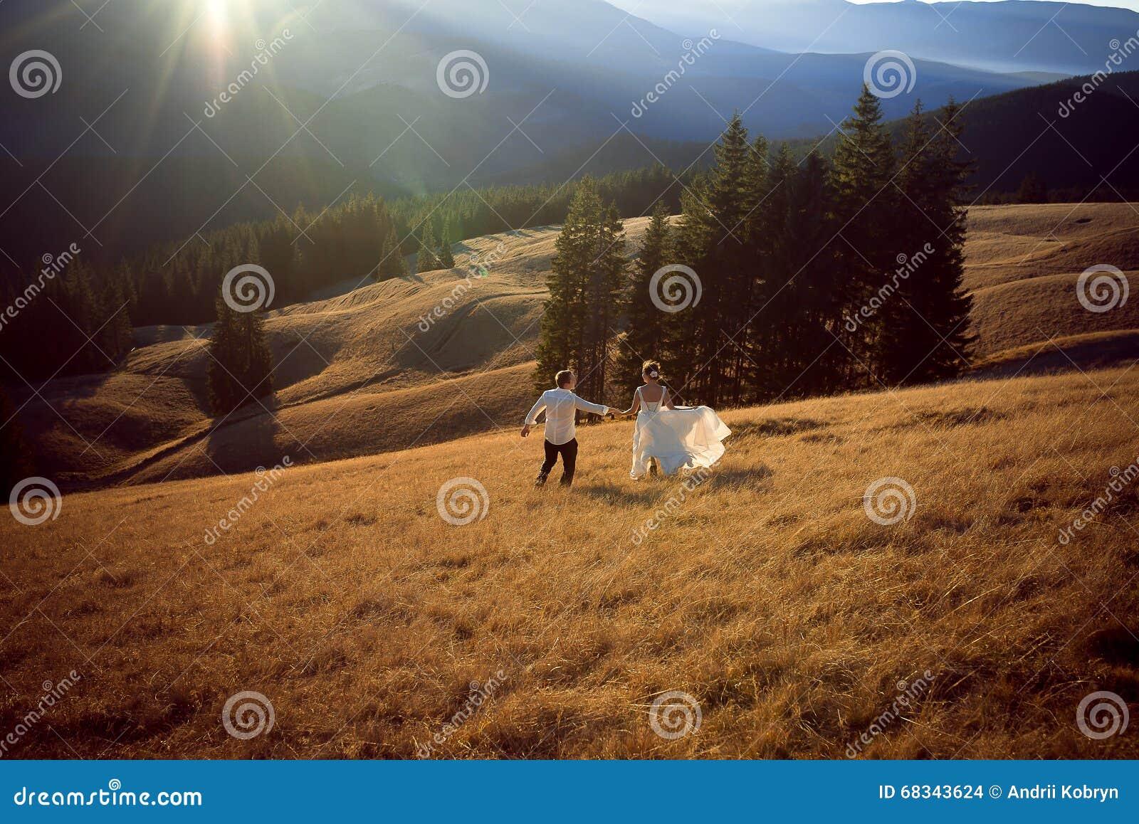 Ευτυχές γαμήλιο ζεύγος που τρέχει και που έχει τη διασκέδαση στον τομέα που περιβάλλεται από τα βουνά