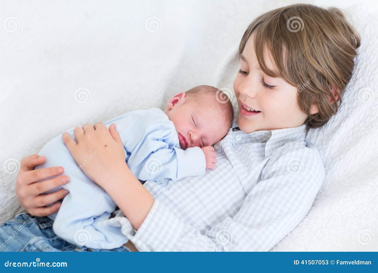 Ευτυχές γελώντας αγόρι που κρατά το νεογέννητο αδελφό μωρών ύπνου του