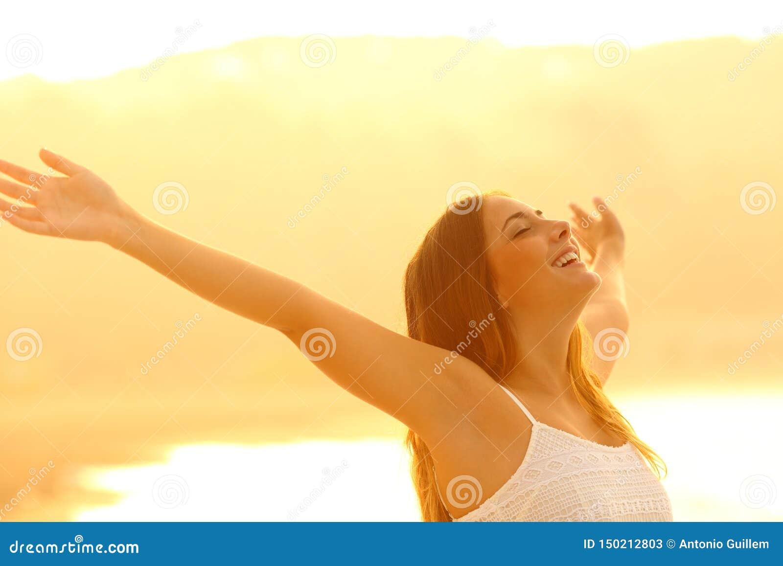 Ευτυχές γυναικών οπλίζει το καθαρό αέρα αναπνοής στο ηλιοβασίλεμα