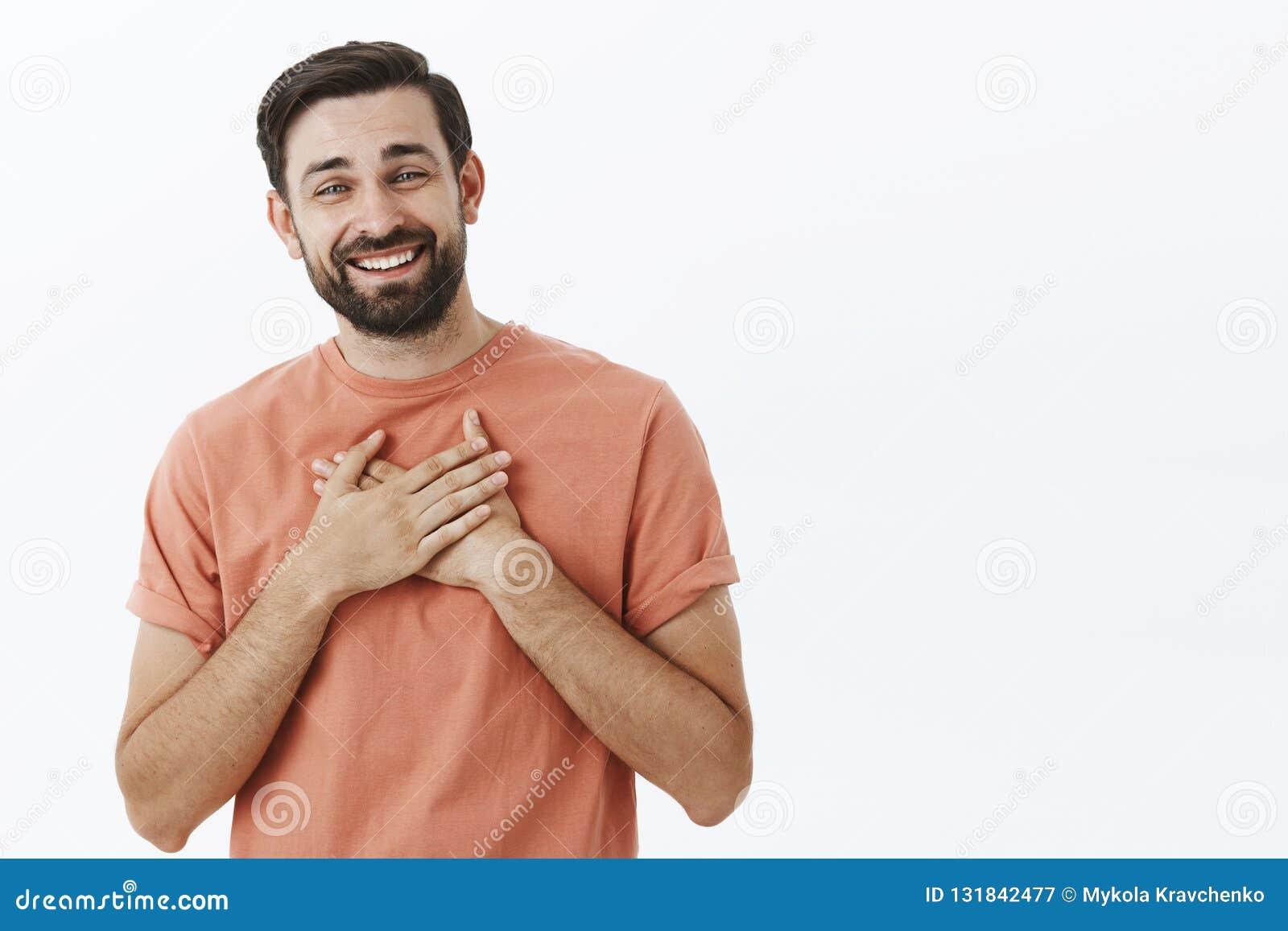Ευτυχές ευχαριστημένο και ευγνώμον ενήλικο ευρωπαϊκό άτομο με τη γενειάδα στους ρόδινους φοίνικες εκμετάλλευσης μπλουζών στην καρ