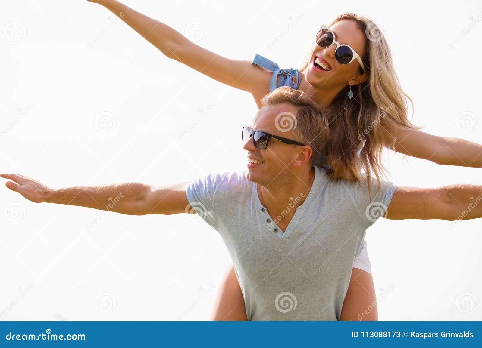 Ευτυχές ζεύγος με τα ευρέα όπλα που πετούν στον αέρα