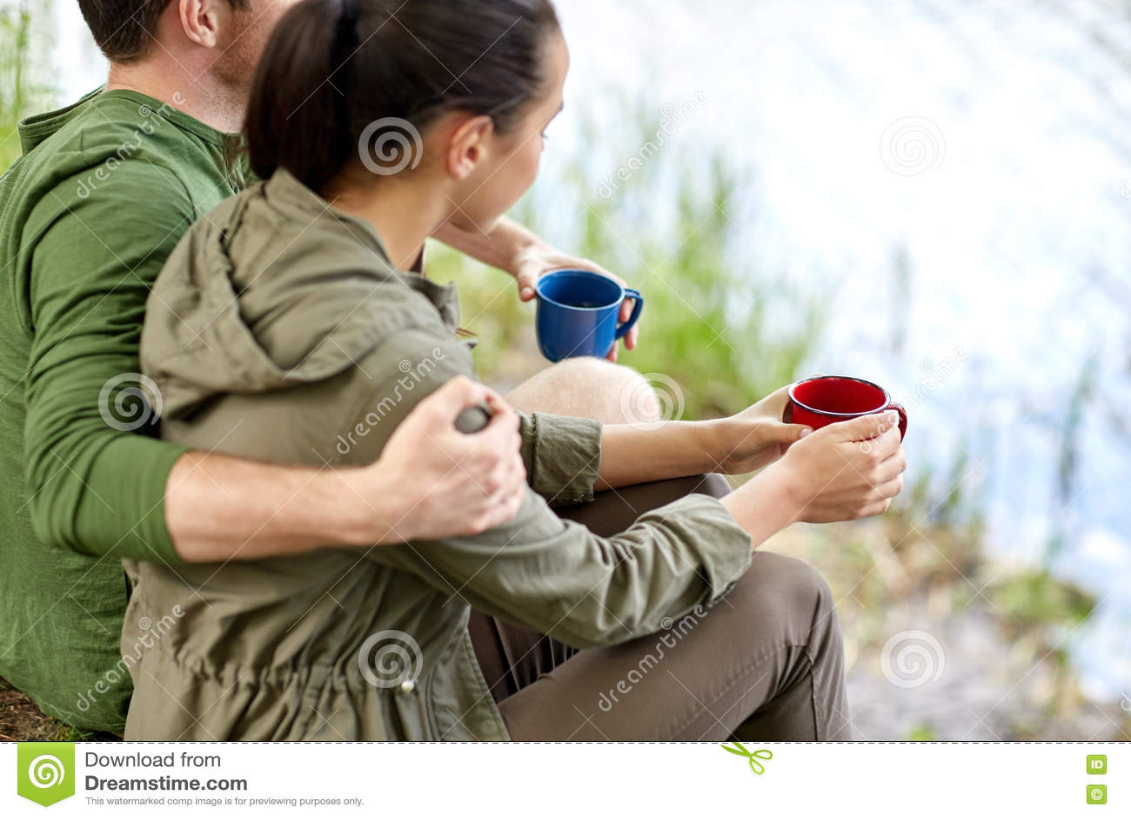 Ευτυχές ζεύγος με τα φλυτζάνια που πίνει στη φύση