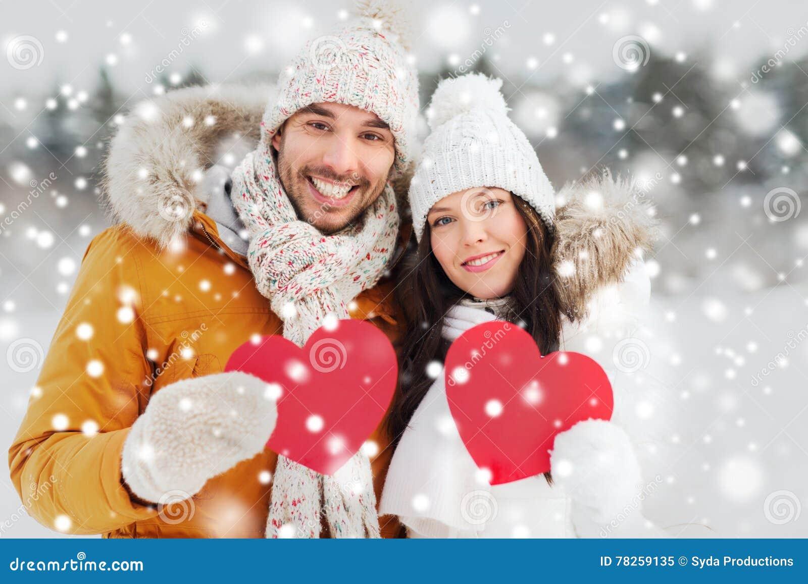 Ευτυχές ζεύγος με τις κόκκινες καρδιές πέρα από το χειμερινό τοπίο