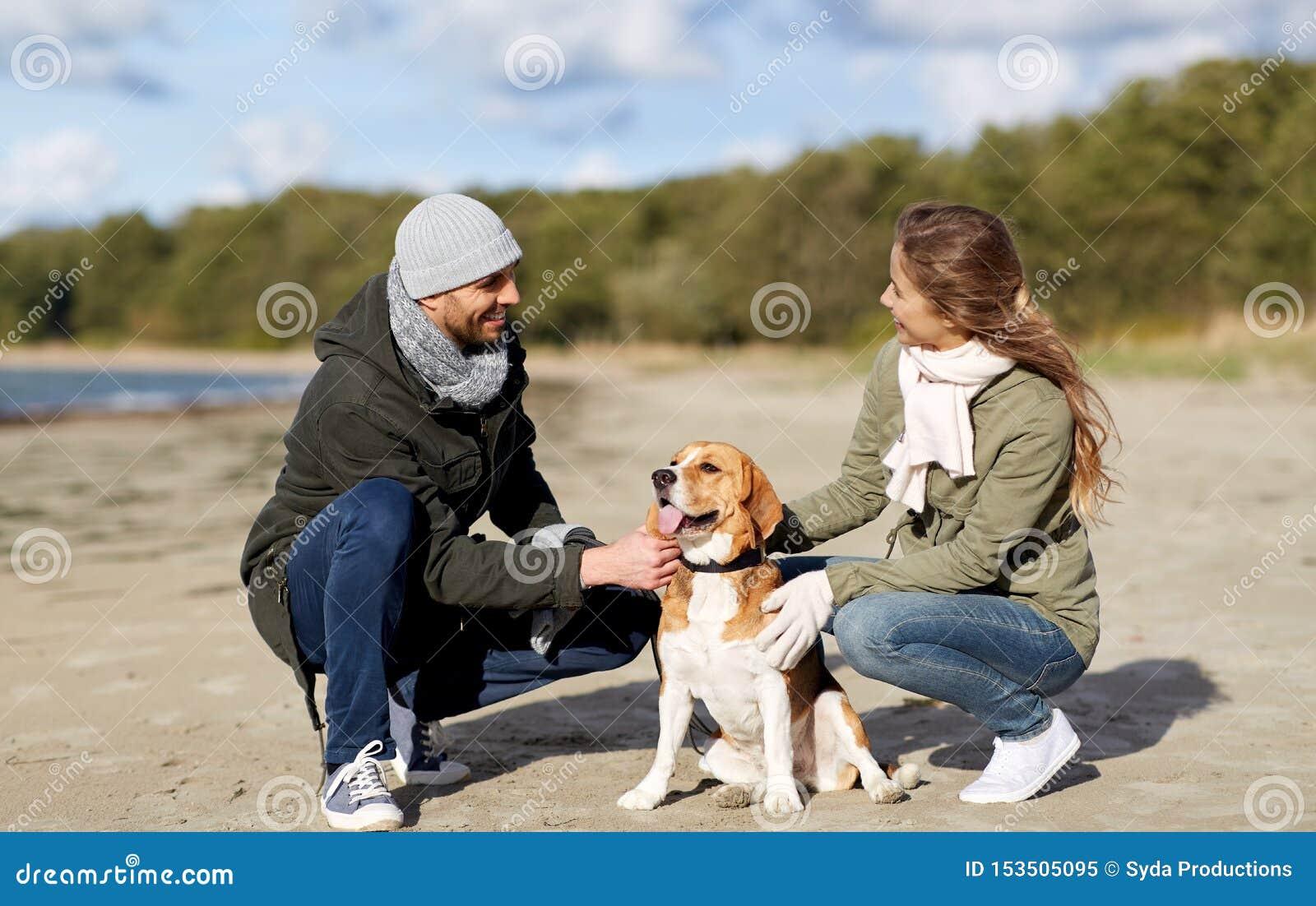 Ευτυχές ζεύγος με το σκυλί λαγωνικών στην παραλία φθινοπώρου