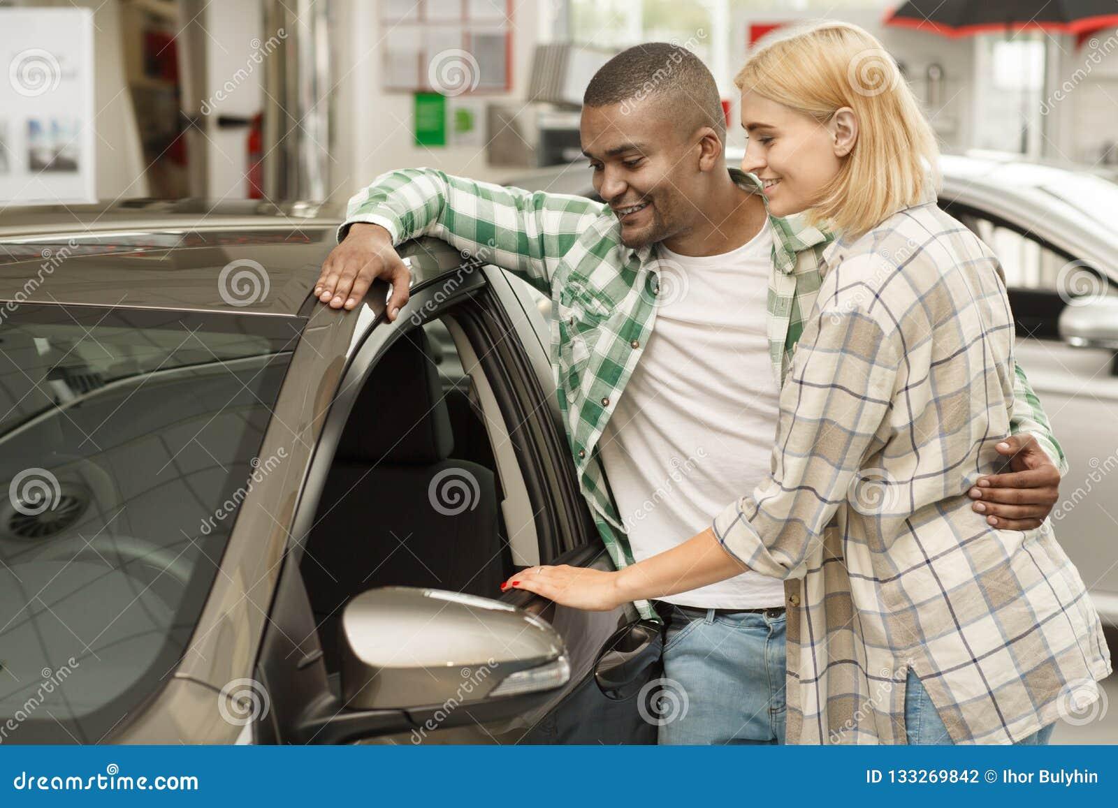 Ευτυχές ζεύγος που αγοράζει το νέο αυτοκίνητο μαζί στον αντιπρόσωπο