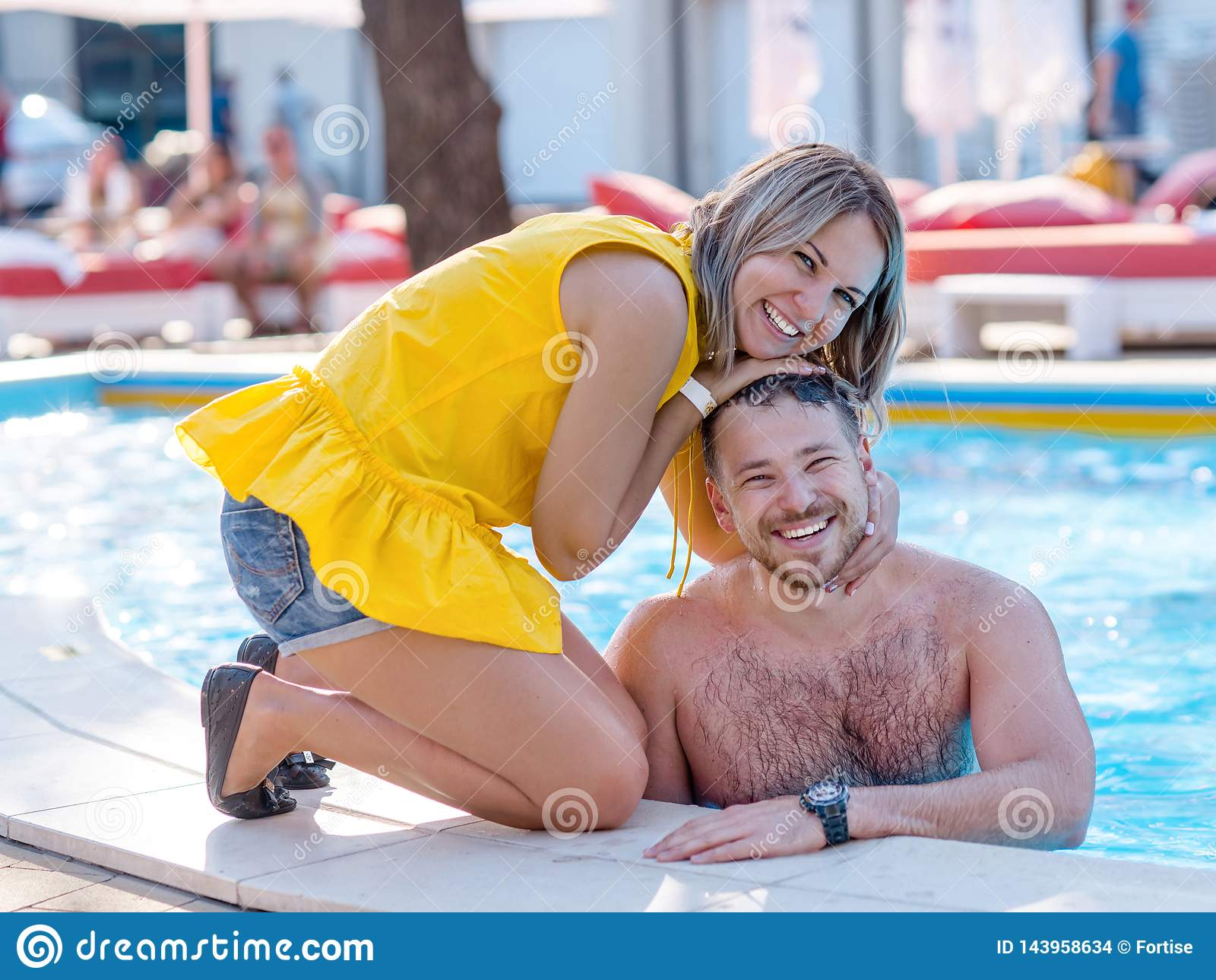 Ευτυχές ζεύγος που απολαμβάνει το καλοκαίρι ν μια πισίνα θερέτρου διακοπών