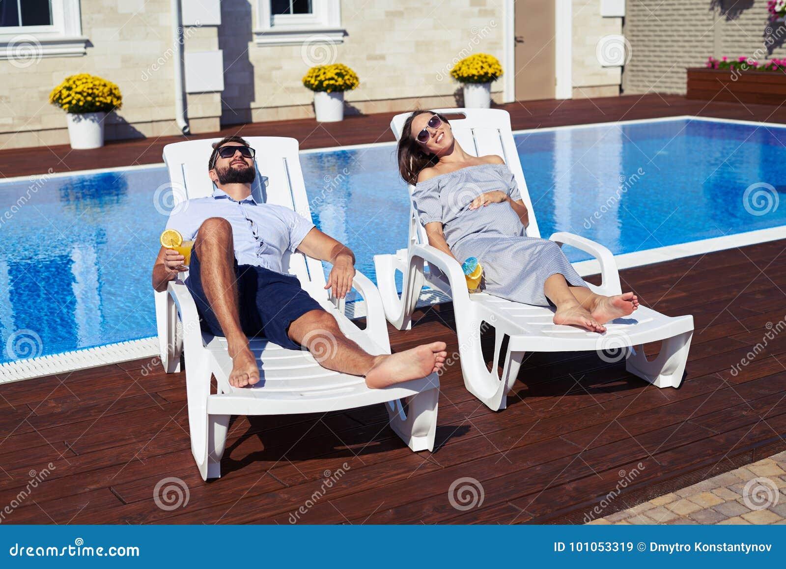 Ευτυχές ζεύγος που βρίσκεται στις καρέκλες σαλονιών μπροστά από το σπίτι με τη λίμνη