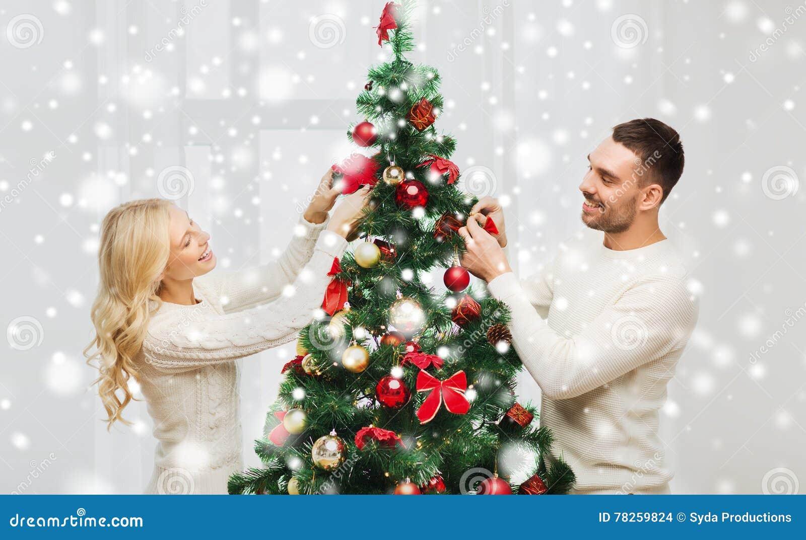 Ευτυχές ζεύγος που διακοσμεί το χριστουγεννιάτικο δέντρο στο σπίτι