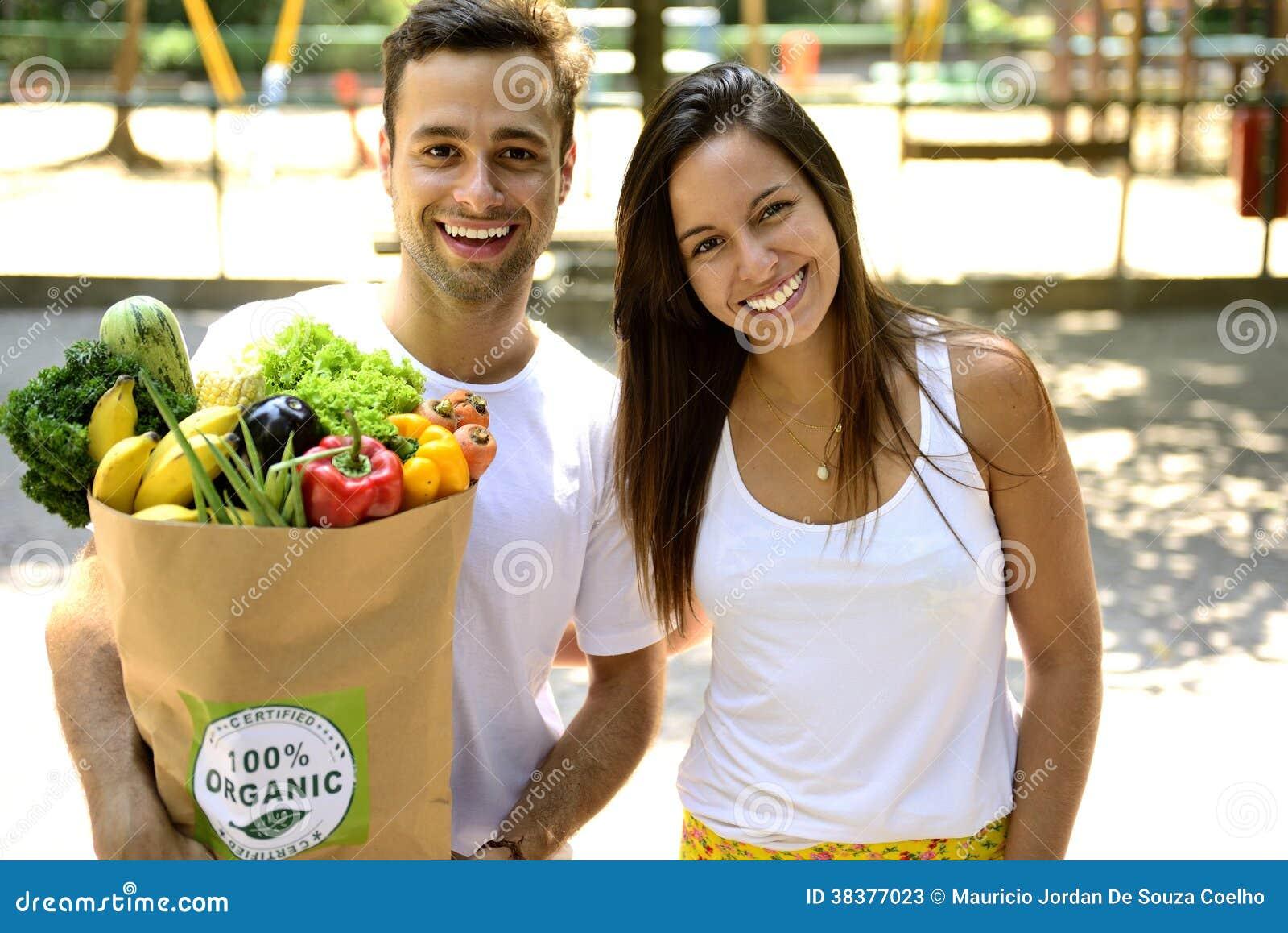 Ευτυχές ζεύγος που φέρνει ένα ανακύκλωσης σύνολο τσαντών εγγράφου των οργανικών φρούτων λαχανικών ANS.