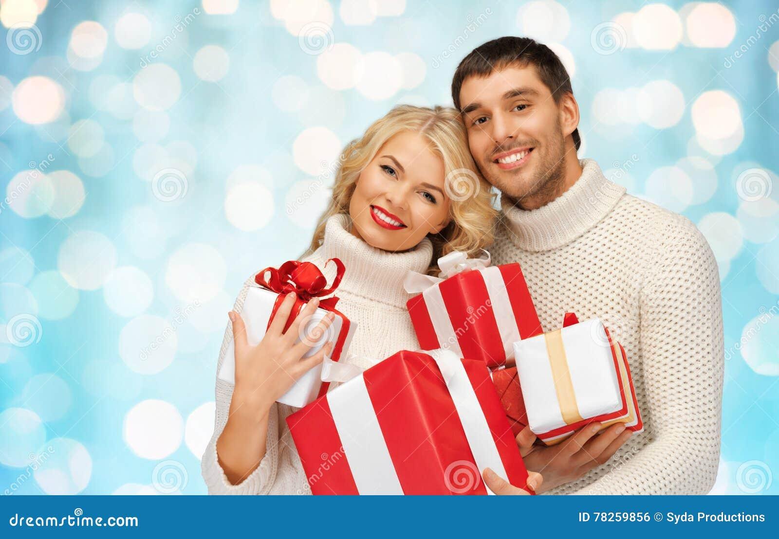 Ευτυχές ζεύγος στα πουλόβερ που κρατά τα δώρα Χριστουγέννων