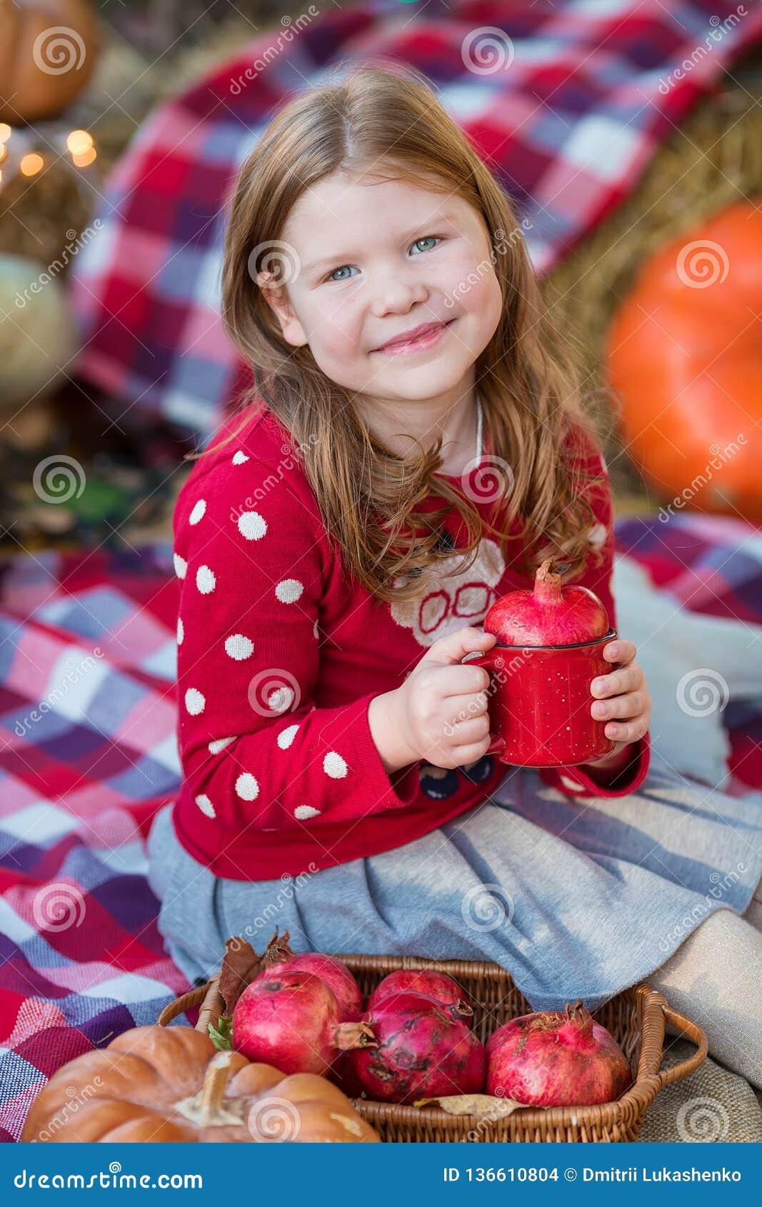 Ευτυχές κορίτσι παιδιών με την κολοκύθα υπαίθρια στο πάρκο αποκριών