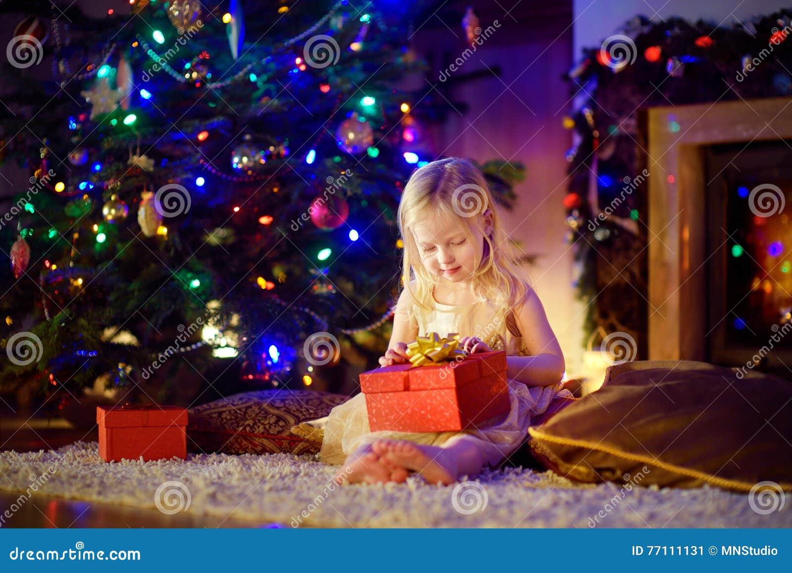 Ευτυχές κορίτσι που ανοίγει το μαγικό δώρο Χριστουγέννων από μια εστία