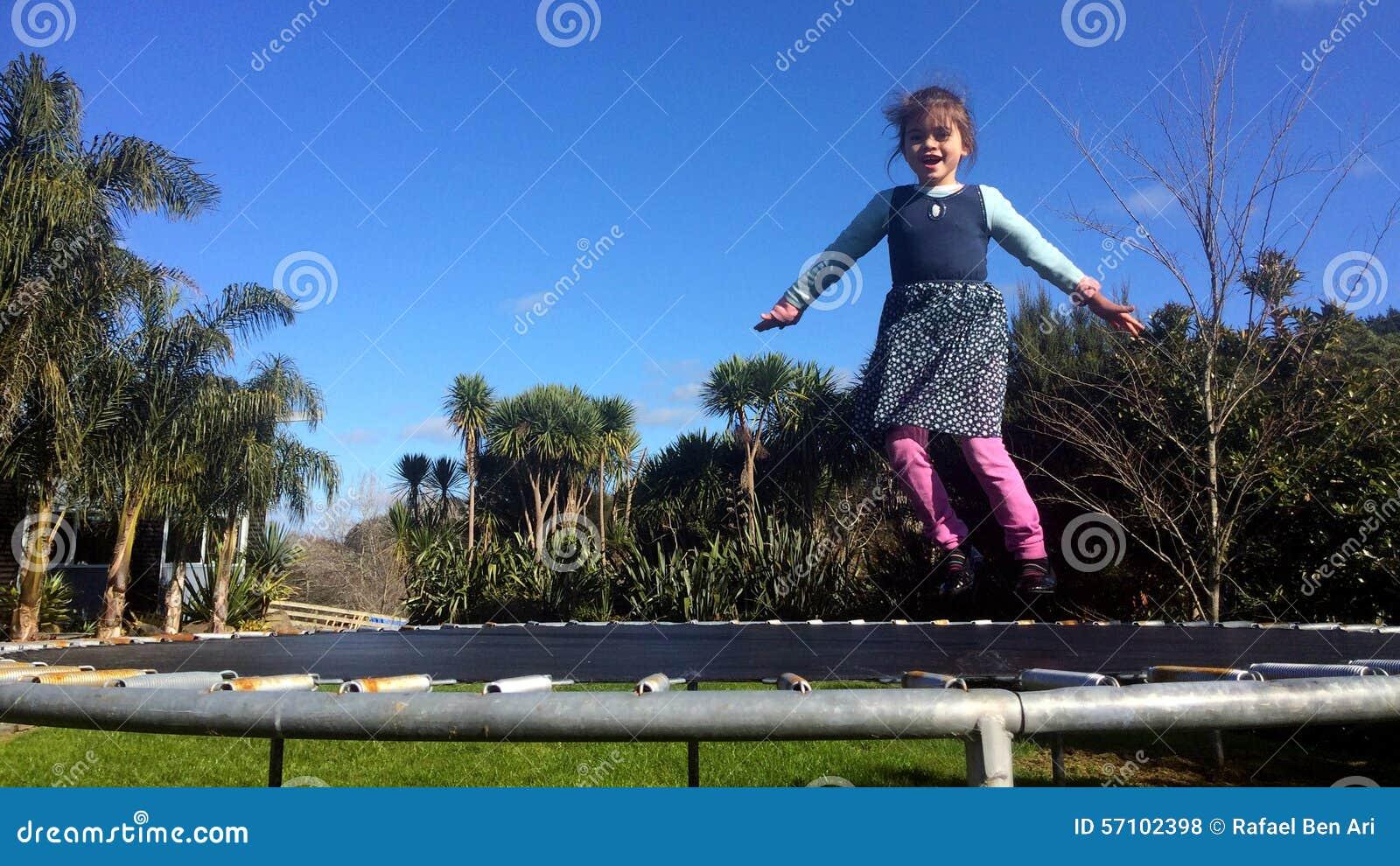 Ευτυχές μικρό κορίτσι που αναπηδά στο τραμπολίνο