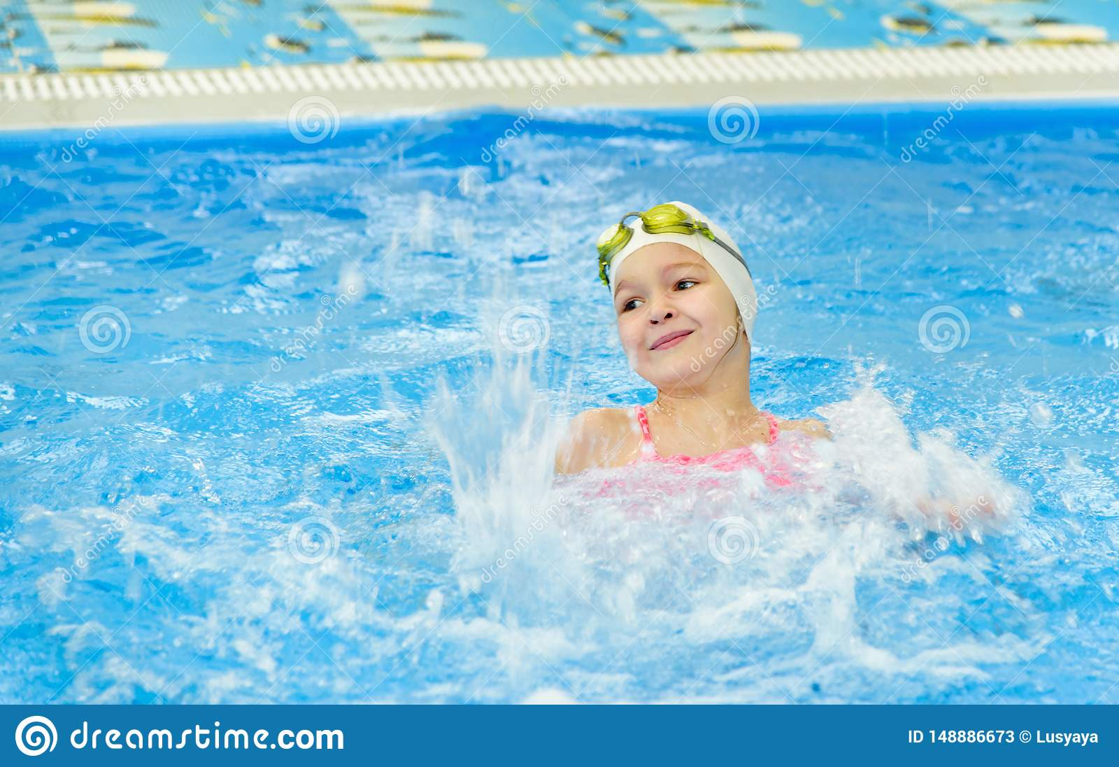 Ευτυχές μικρό κορίτσι που κολυμπά στη λίμνη Το καυκάσιο παιδί παίζει τη διασκέδαση στη λίμνη παιδικών σταθμών