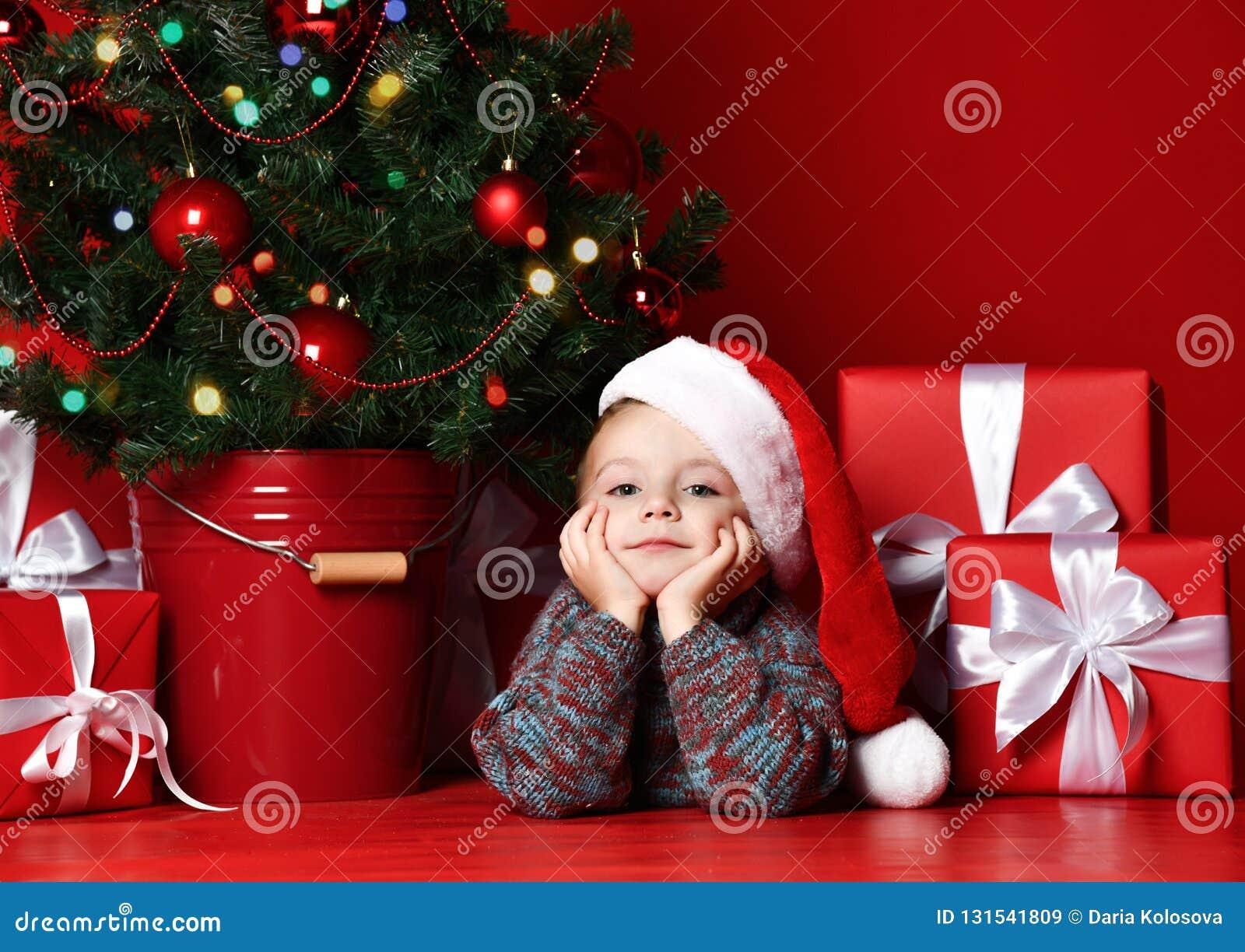 ευτυχές νέο έτος Χριστο&upsilo Πορτρέτο του παιδιού στο κόκκινο καπέλο Santa που περιμένει τα δώρα Χριστουγέννων