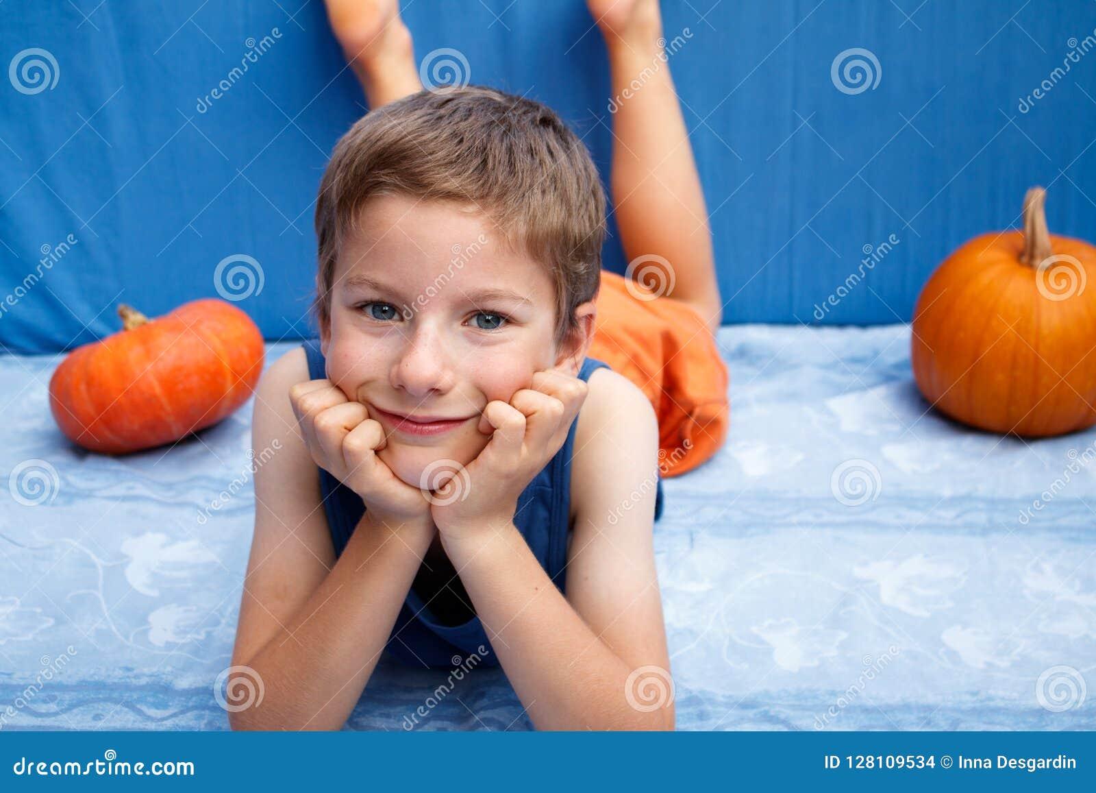 Ευτυχές νέο αγόρι που ξαπλώνει στο μπλε υπόβαθρο με τις κολοκύθες