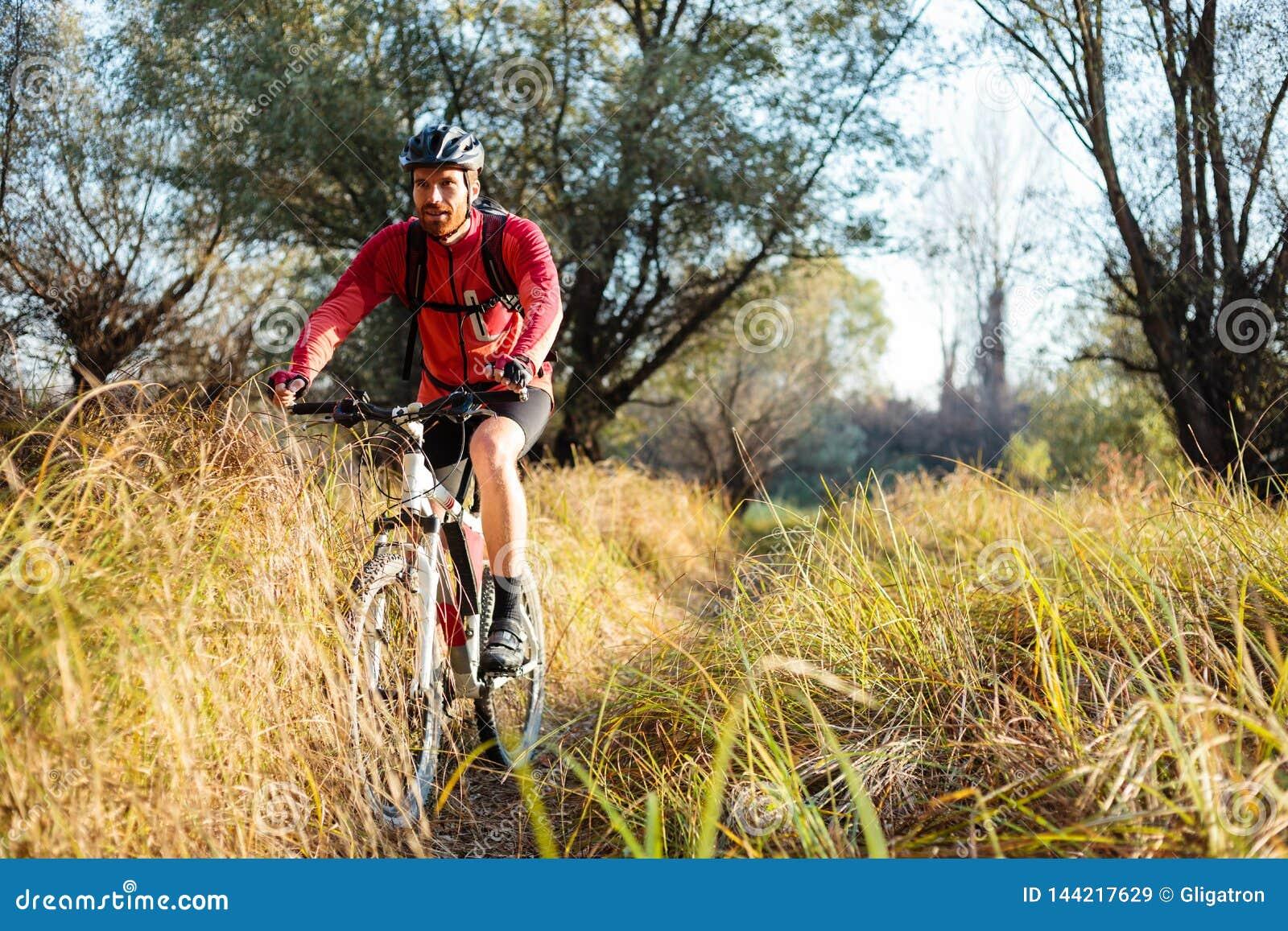 Ευτυχές νέο γενειοφόρο ποδήλατο βουνών ατόμων οδηγώντας κατά μήκος μιας πορείας μέσω της ψηλής χλόης