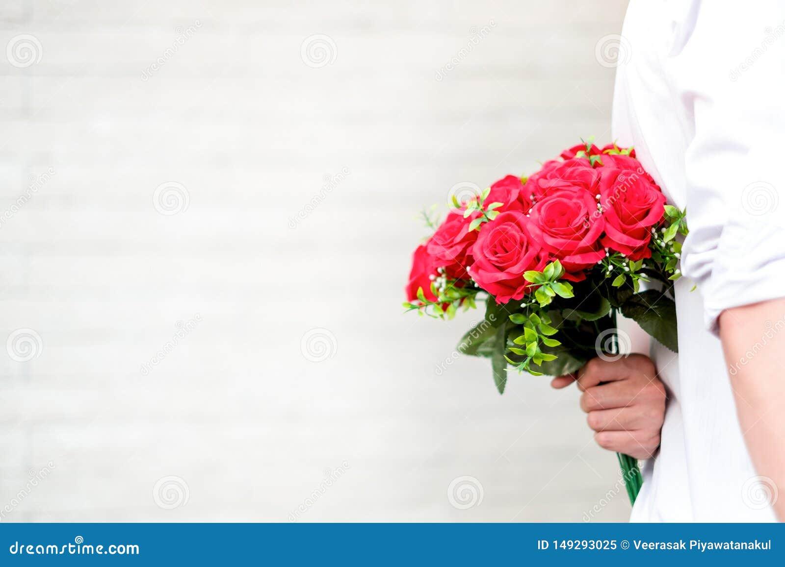 Ευτυχές νέο ζεύγος ερωτευμένο αγκάλιασμα και κόκκινα τριαντάφυλλα κρατήματος στα χέρια για την έκπληξη της φίλης του, έννοια ζευγ