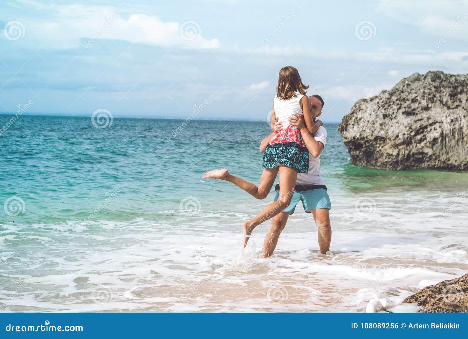Ευτυχές νέο ζεύγος μήνα του μέλιτος που έχει τη διασκέδαση στην παραλία Ωκεάνιες, τροπικές διακοπές στο νησί του Μπαλί, Ινδονησία