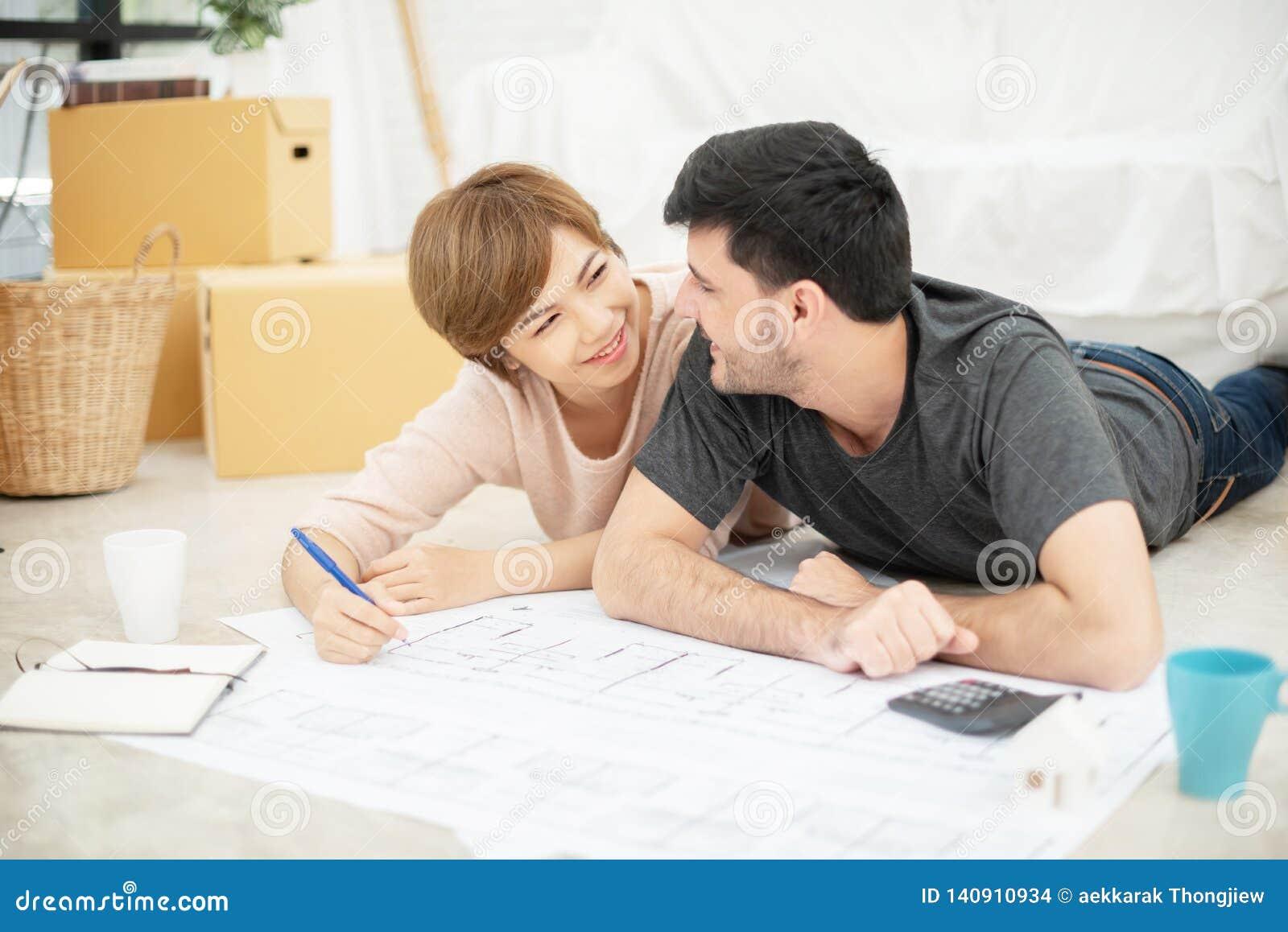 Ευτυχές νέο ζεύγος με τα σχεδιαγράμματα που προγραμματίζει το καινούργιο σπίτι τους