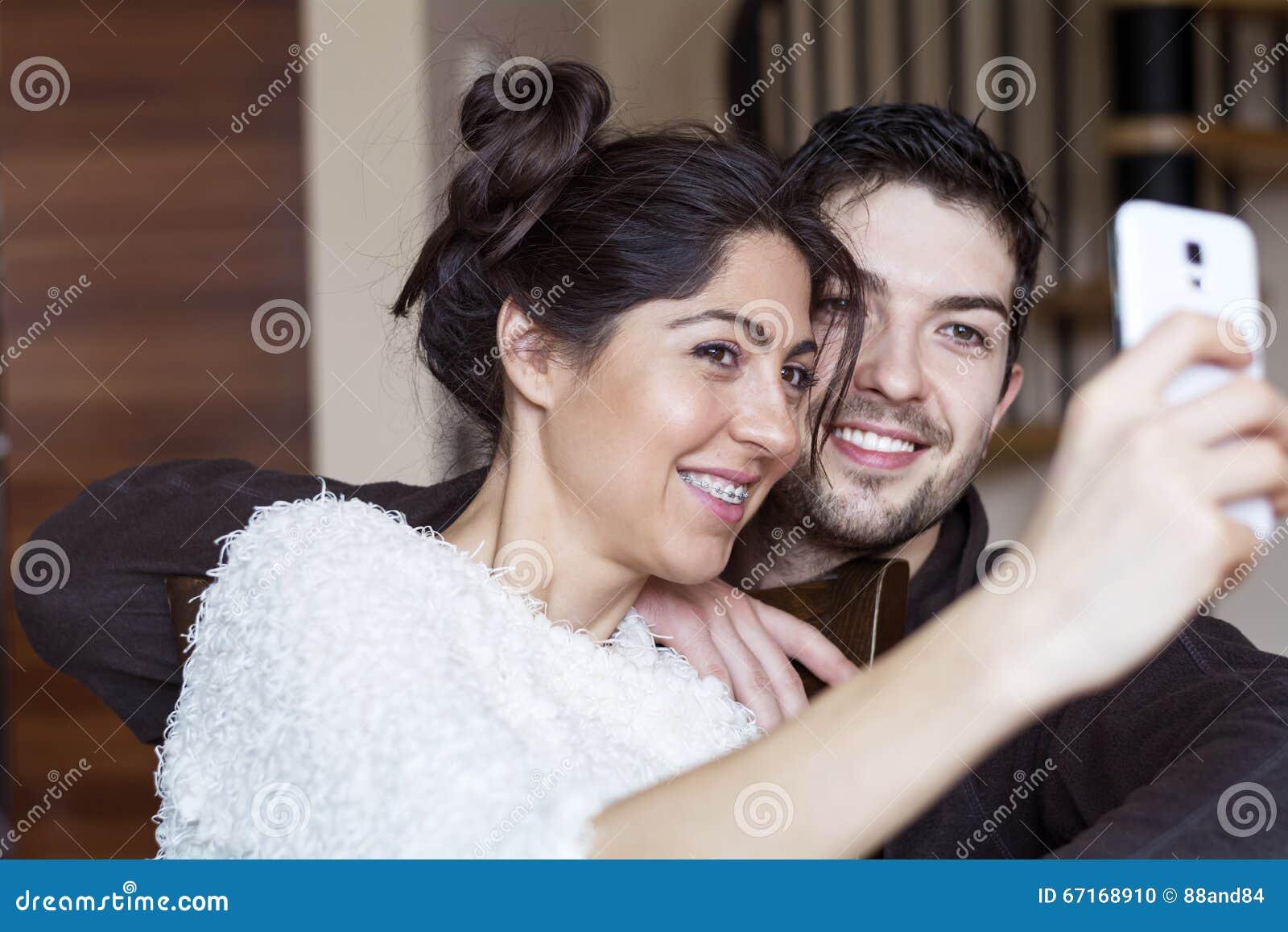 Ευτυχές νέο ζεύγος που κάνει selfie εσωτερικό