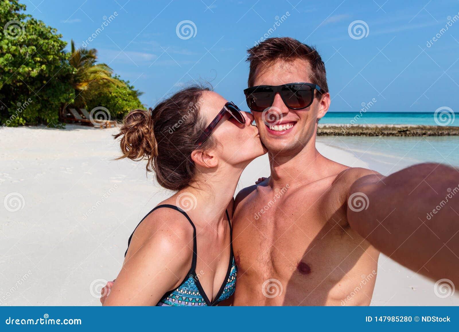 Ευτυχές νέο ζεύγος που παίρνει ένα selfie, ένα τροπικό νησί και ένα σαφές μπλε νερό ως υπόβαθρο Κορίτσι που φιλά το φίλο του